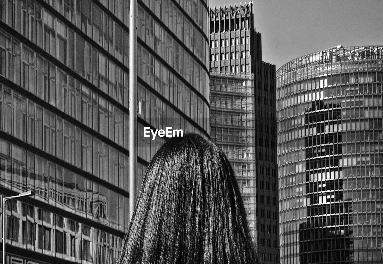 Rear view of woman against modern buildings