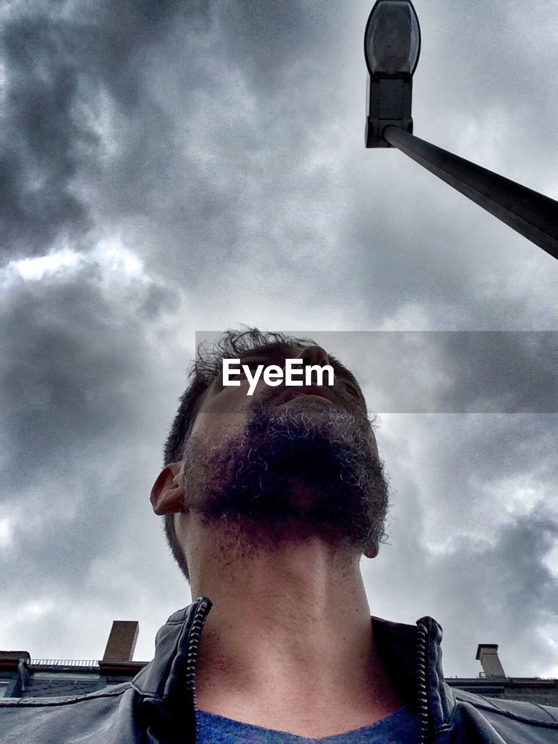 Low angle view of man against street light and cloudy sky