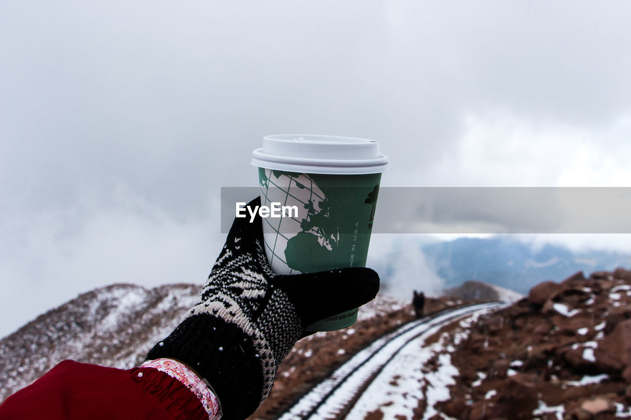 Cropped Image Of Person Holding Coffee Cup On Pikes Peak Against Sky