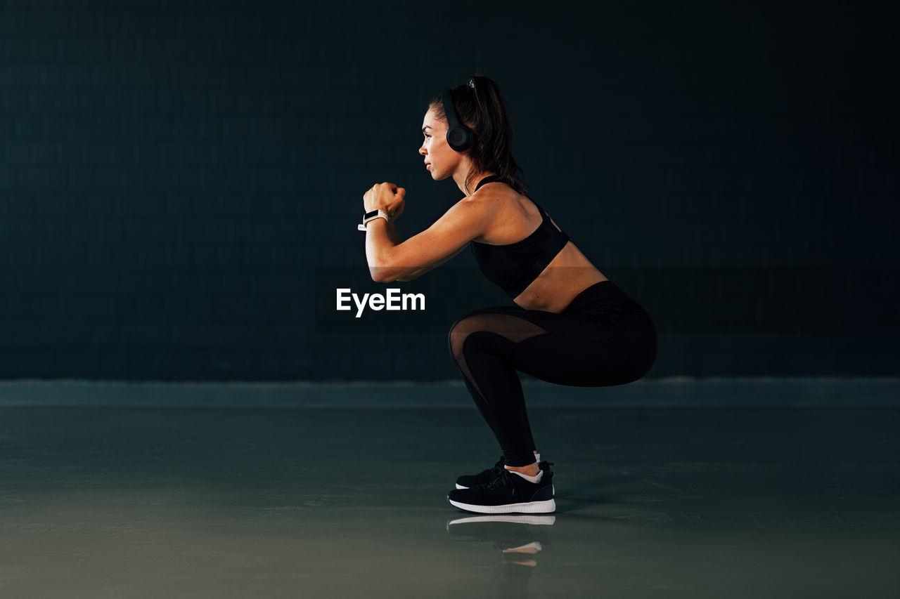 Full length of woman exercising against black background