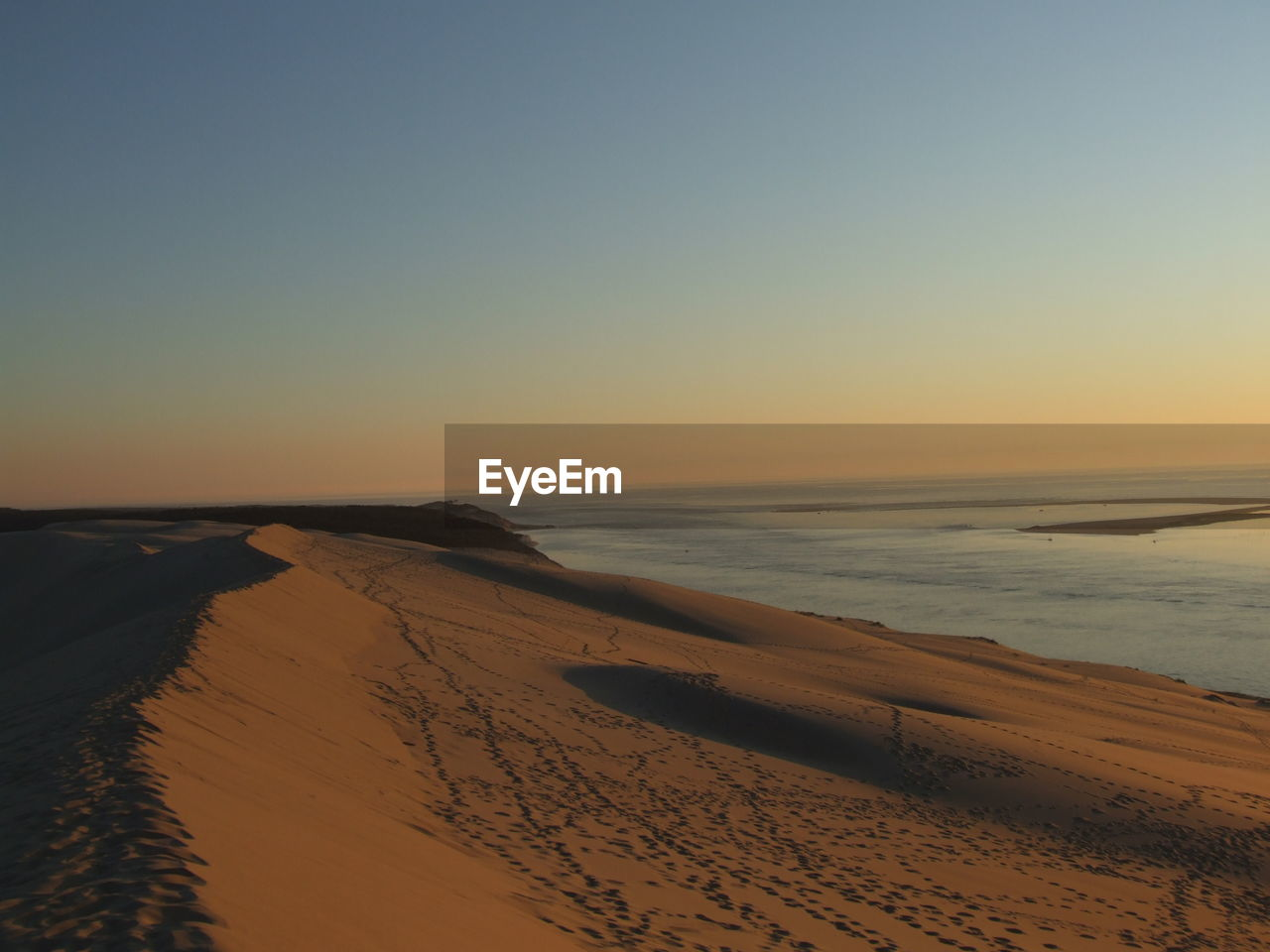 beach, sea, sand, scenics, sunset, beauty in nature, nature, tranquil scene, tranquility, horizon over water, water, clear sky, no people, sky, outdoors, sunlight, vacations, sand dune, wave, day