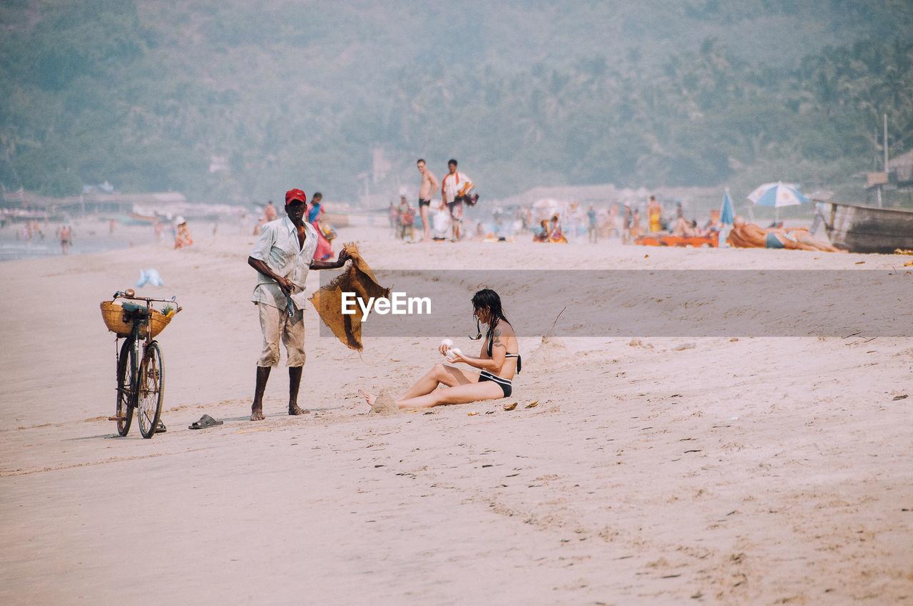 MEN SITTING AT BEACH