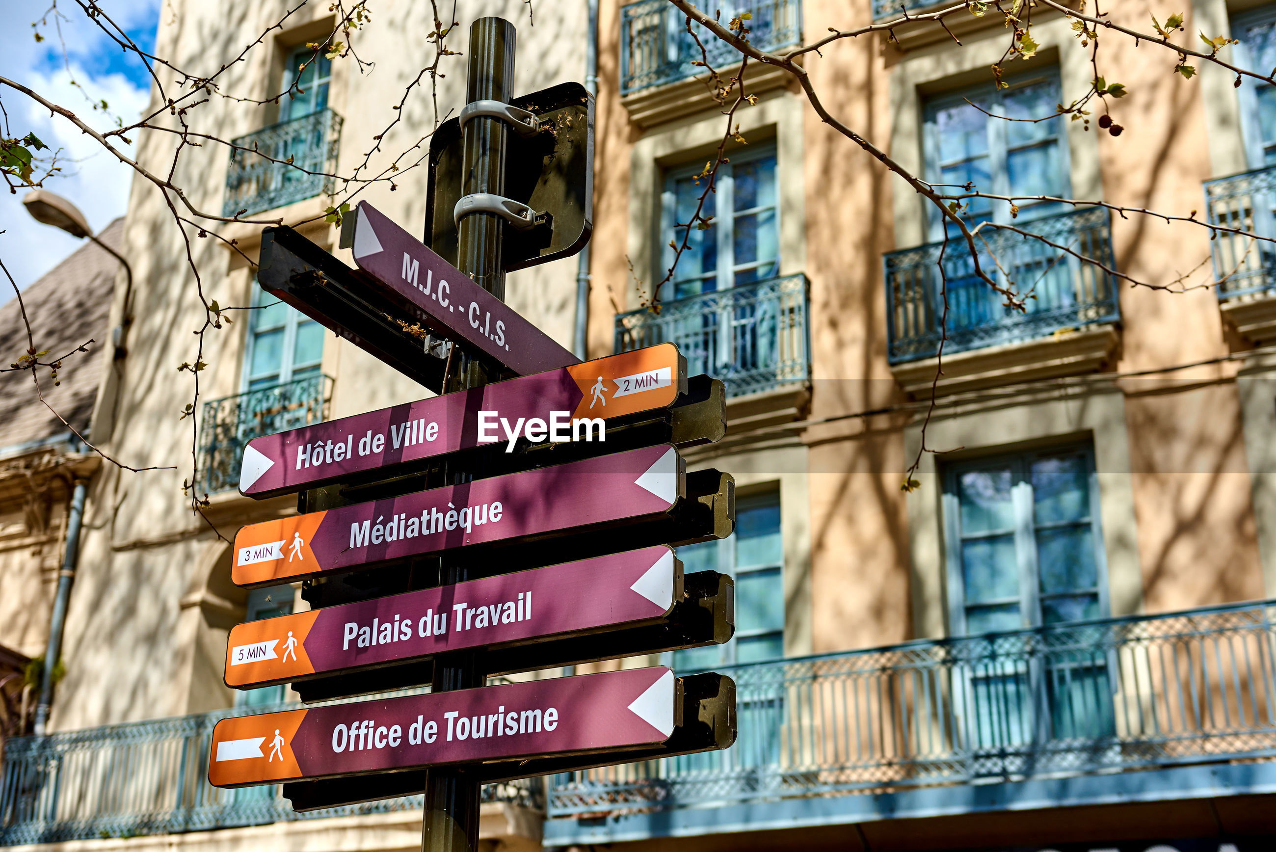 Low angle view of direction signs against building in city