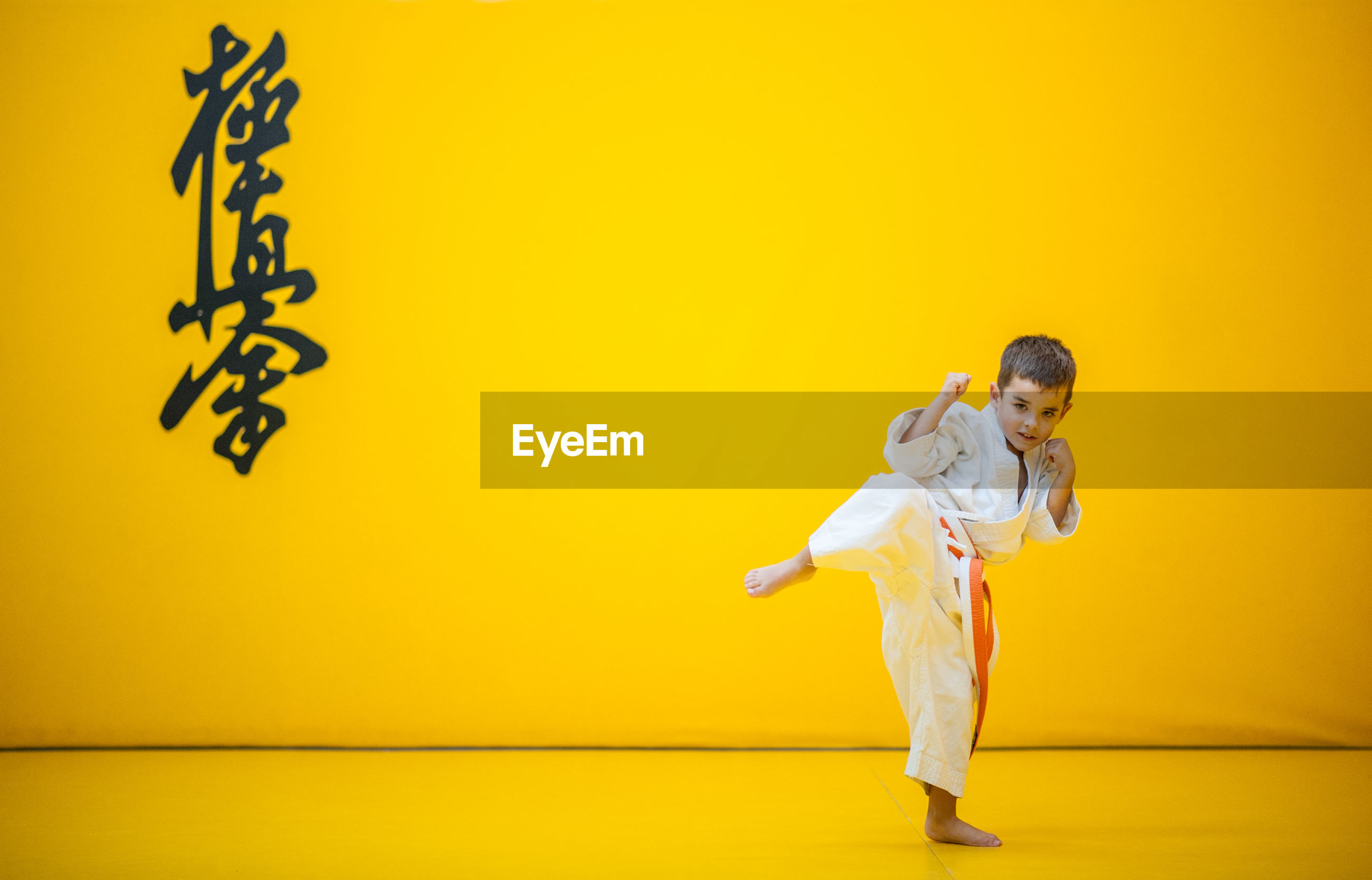 Portrait of cute boy practicing martial arts against yellow wall