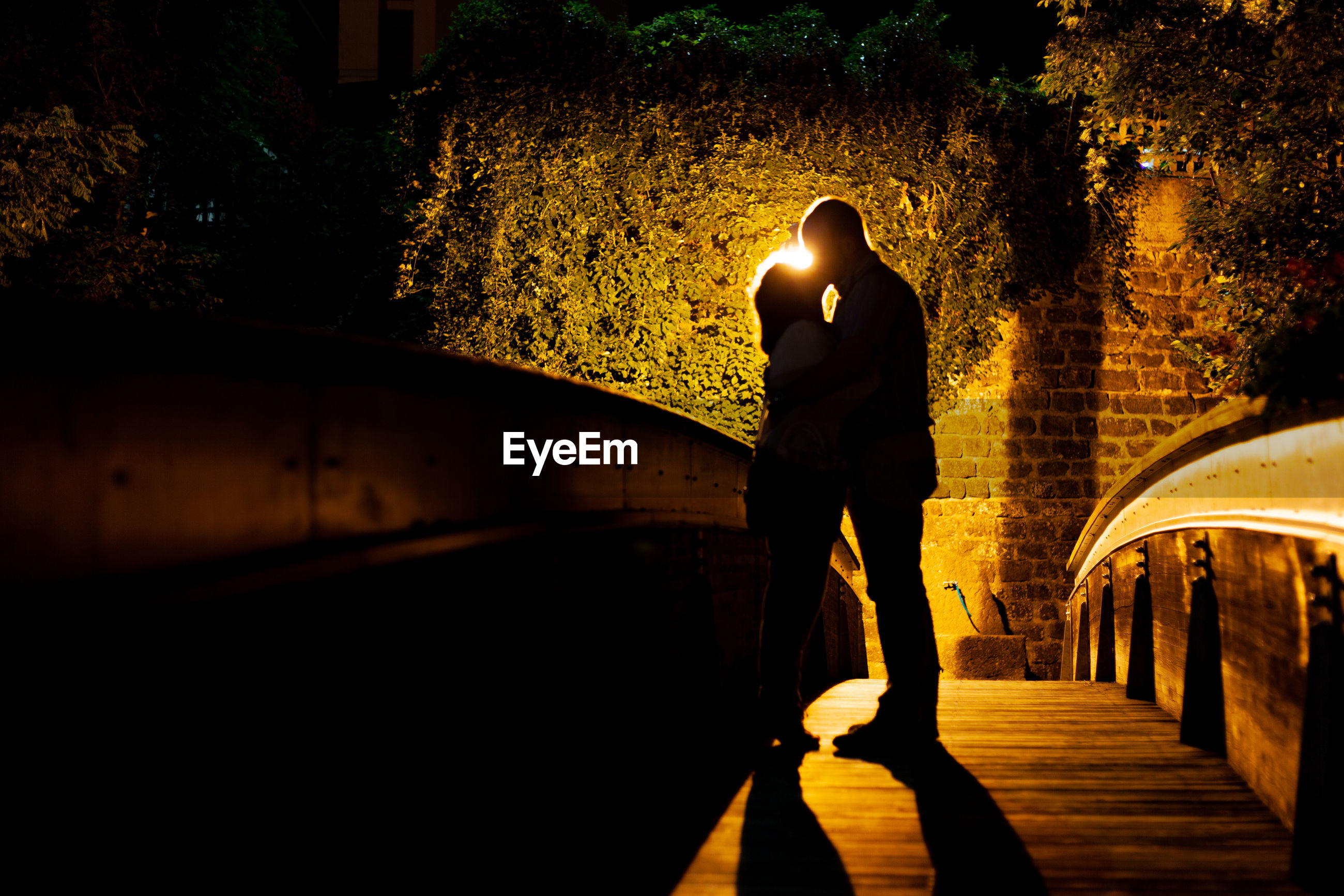 Couple kissing on footbridge at night