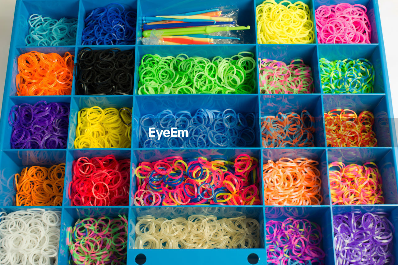 High Angle View Of Colorful Rubber Bands In Plastic Container
