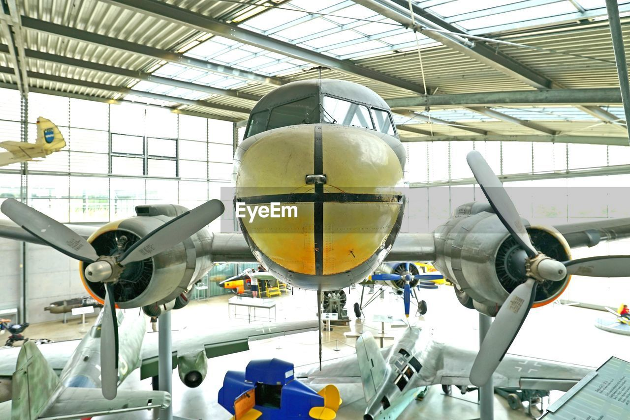airplane, air vehicle, indoors, transportation, aerospace industry, mode of transport, airplane hangar, commercial airplane, low angle view, jet engine, no people, technology, day, clock