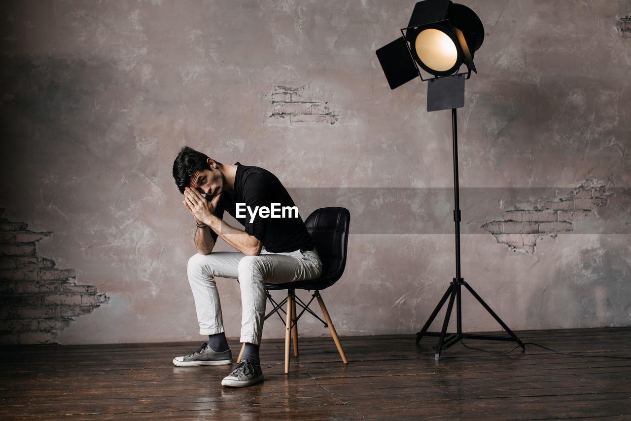 Handsome Man Sitting On Chair At Film Studio