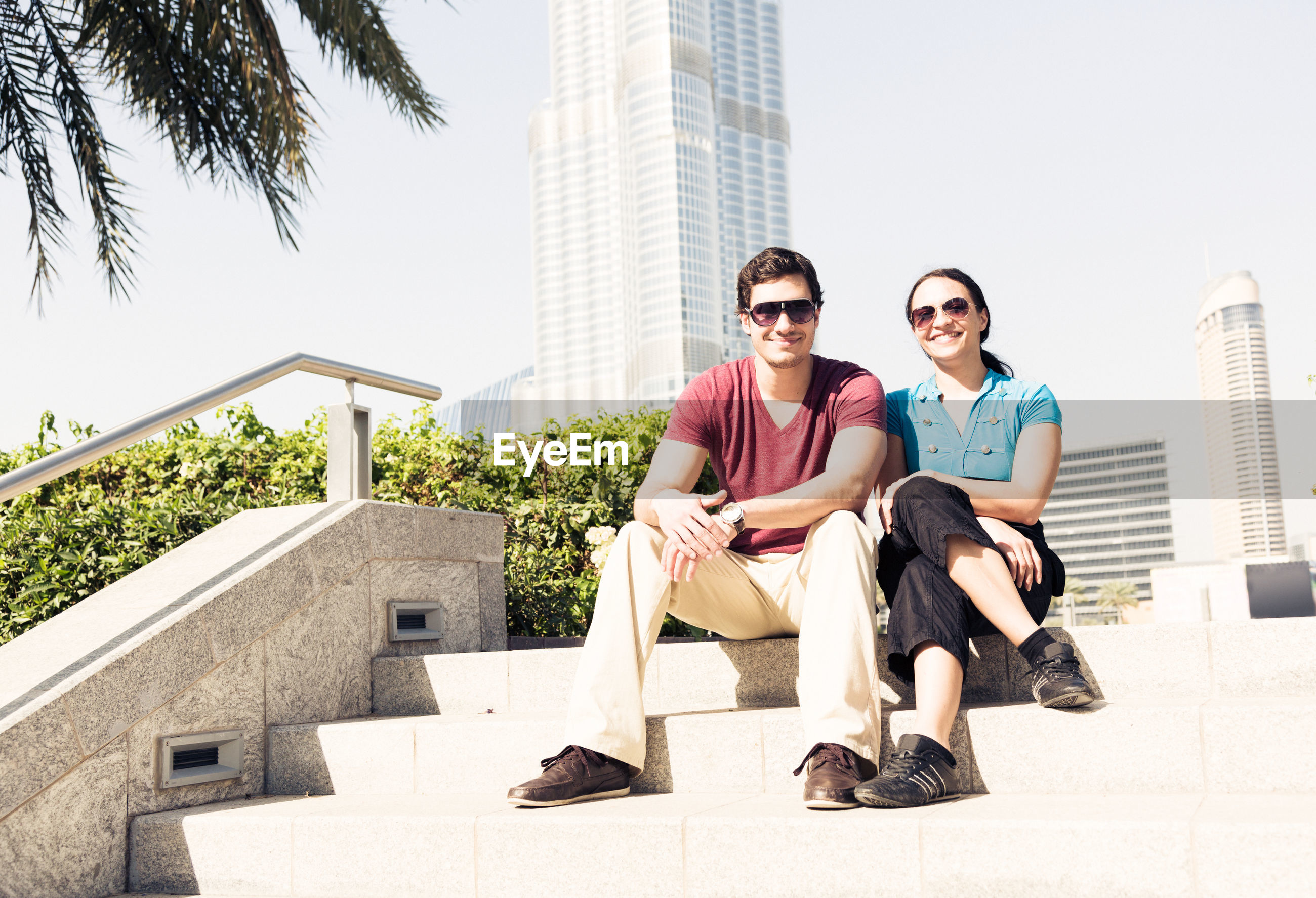 Portrait of smiling young couple sitting on steps