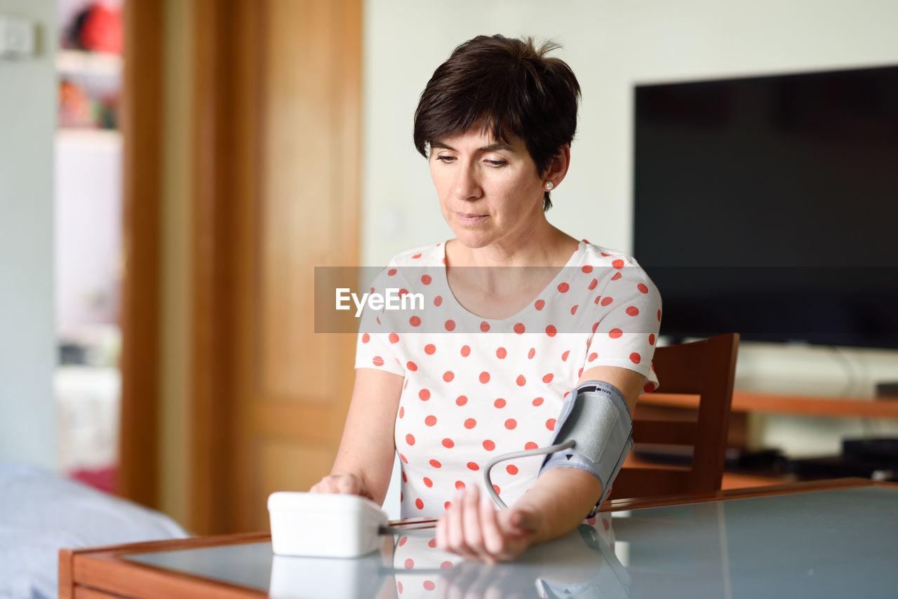 Mature woman examining blood pressure at home
