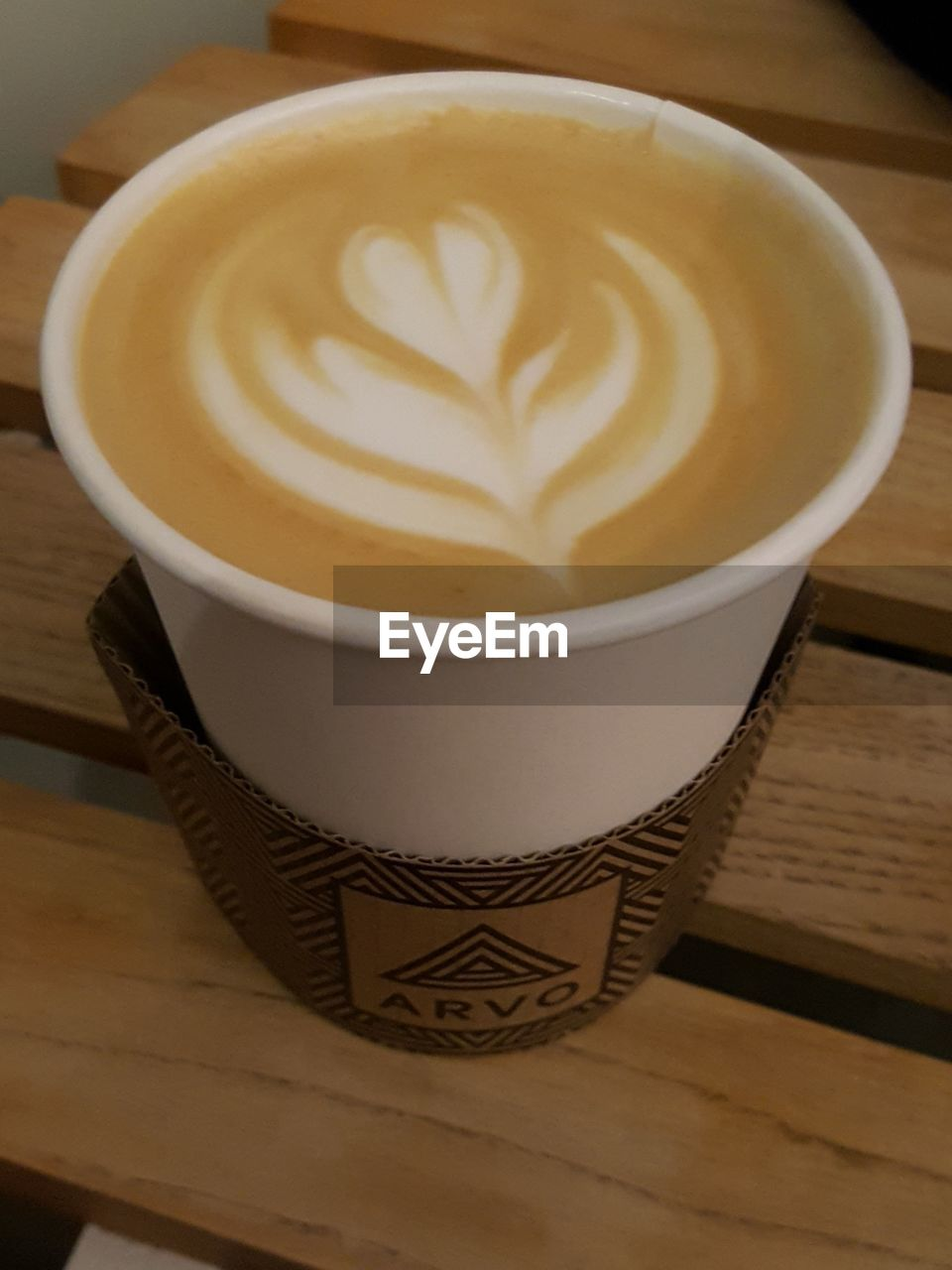 coffee cup, coffee - drink, froth art, drink, frothy drink, refreshment, cappuccino, table, food and drink, design, creativity, latte, art and craft, indoors, high angle view, shape, saucer, close-up, freshness, no people, pattern, wood - material, cafe, healthy eating, thick, mocha, day