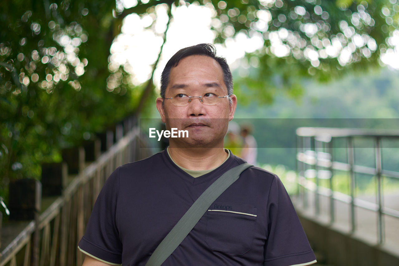 looking at camera, portrait, real people, one person, focus on foreground, front view, lifestyles, men, railing, leisure activity, headshot, day, standing, males, casual clothing, mature adult, nature, adult, outdoors, mature men
