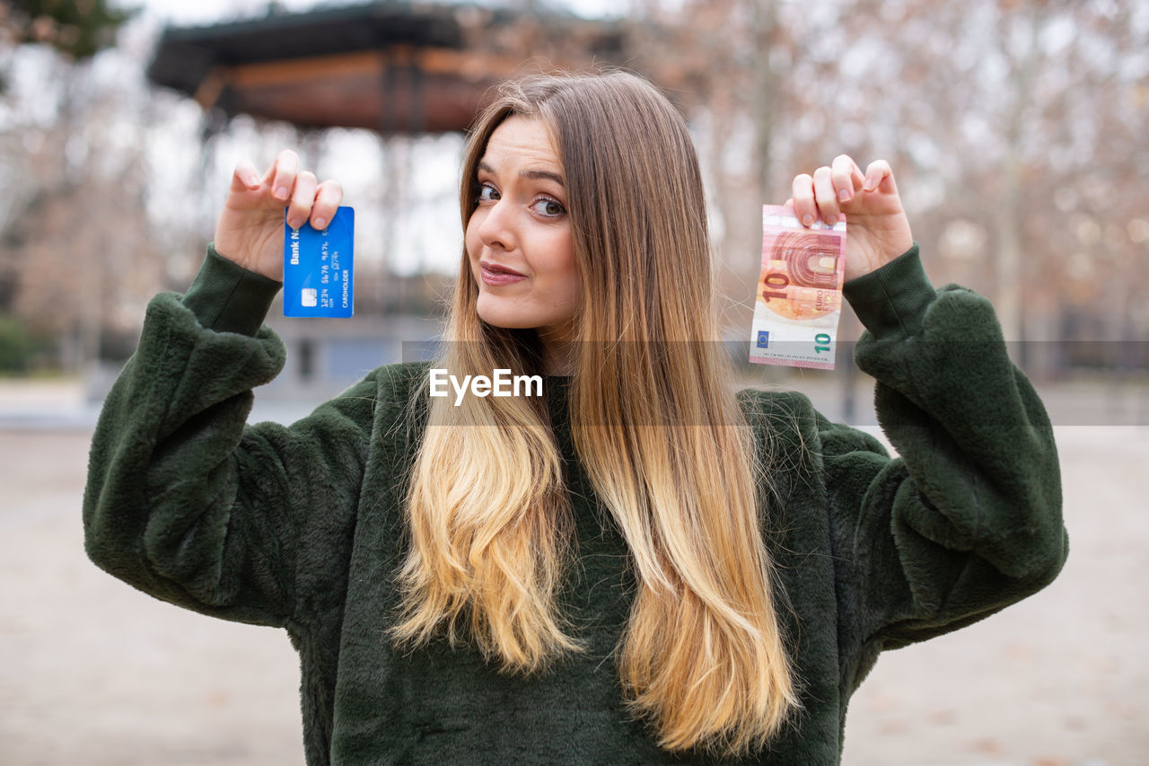 Portrait of woman holding credit card and money while standing outdoors