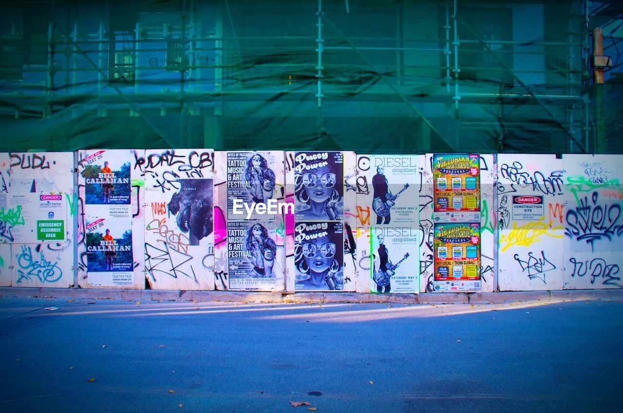 graffiti, city, architecture, built structure, street, group of people, real people, communication, text, building exterior, creativity, people, transportation, road, city life, day, lifestyles, women, sign, multi colored, outdoors