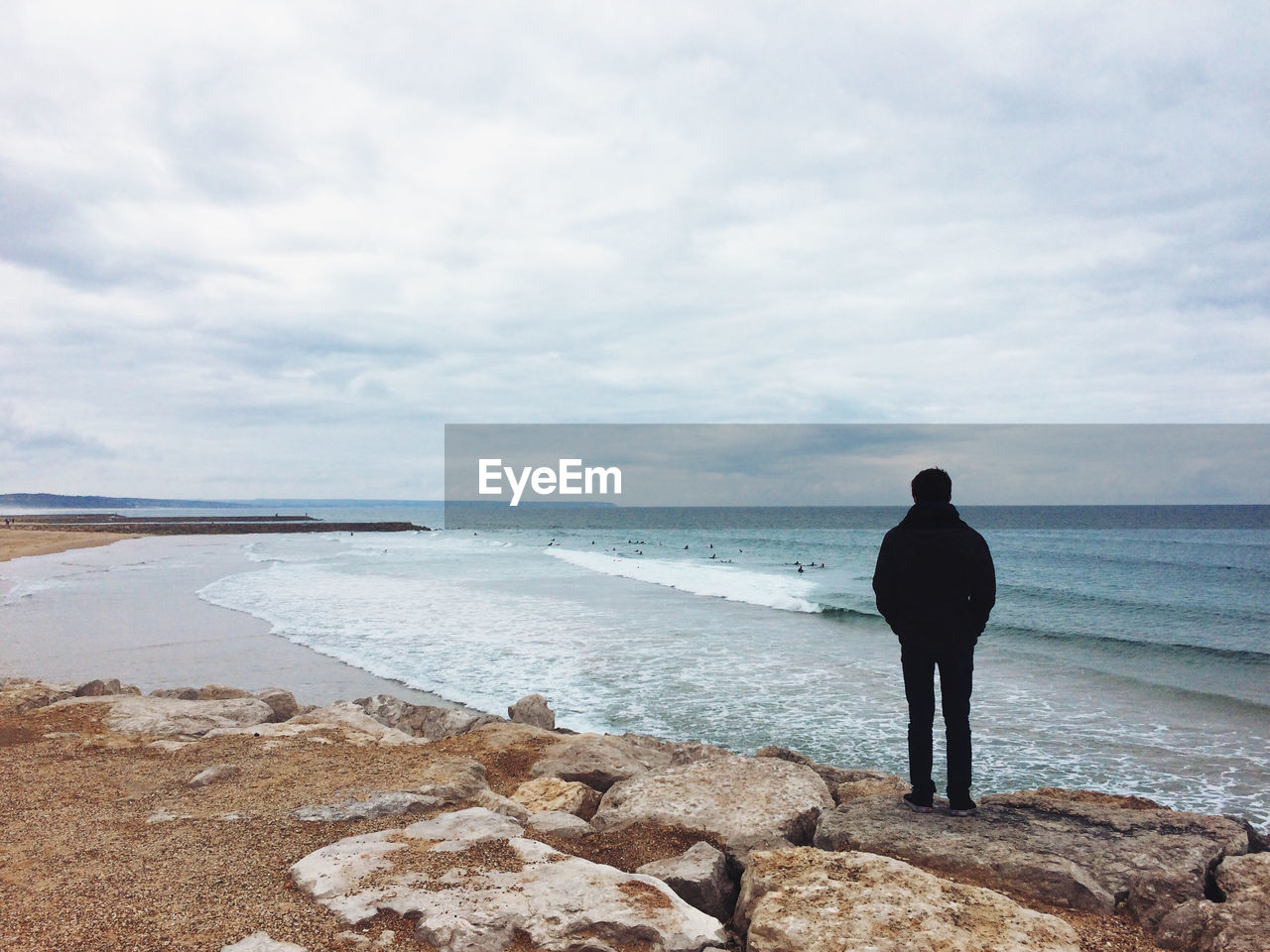 Rear View Of Man Standing At Beach Against Cloudy Sky