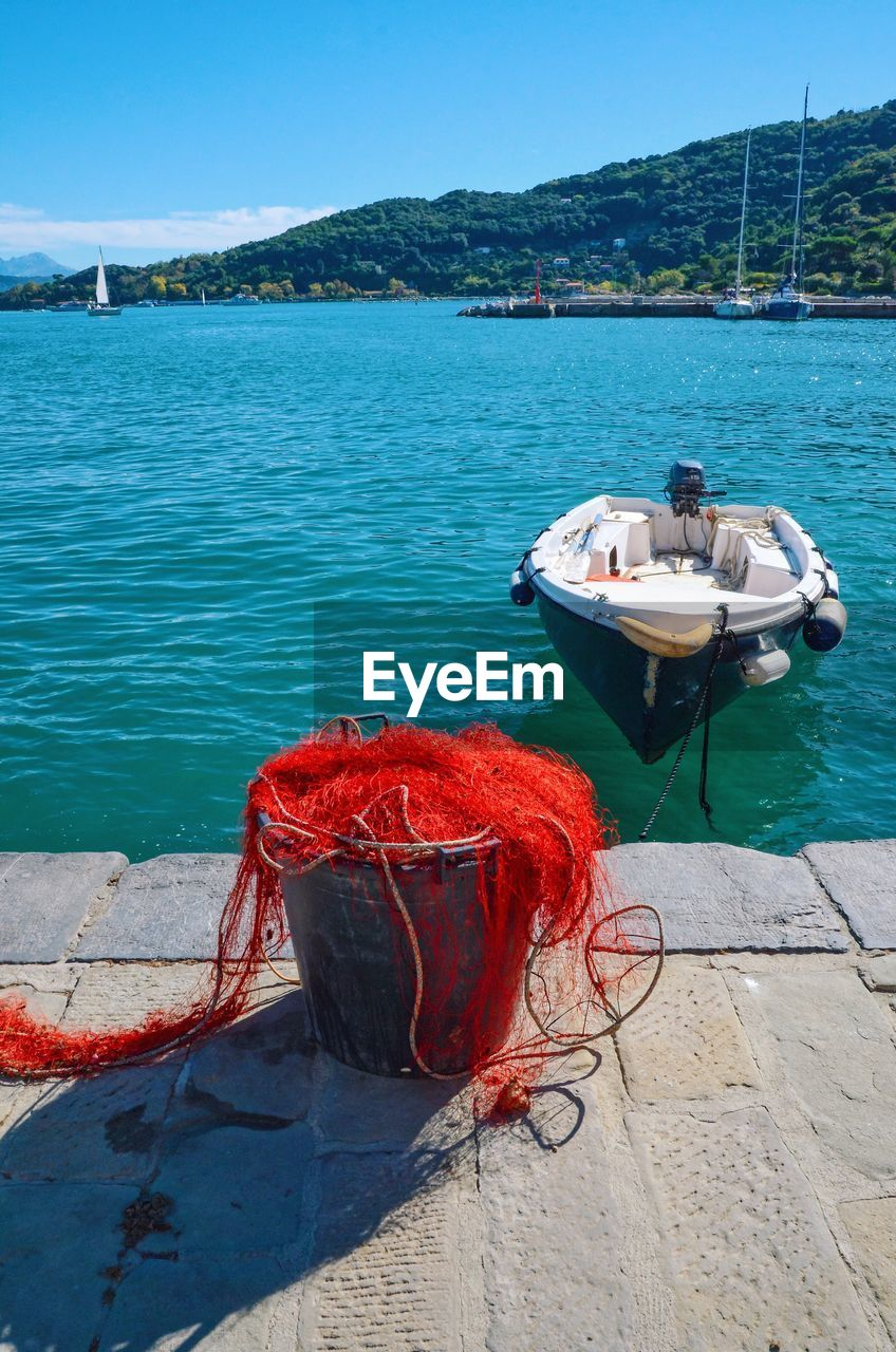 nautical vessel, transportation, mode of transport, water, moored, boat, sea, no people, day, outdoors, rope, nature, red, sunlight, mountain, shadow, harbor, beauty in nature, sky
