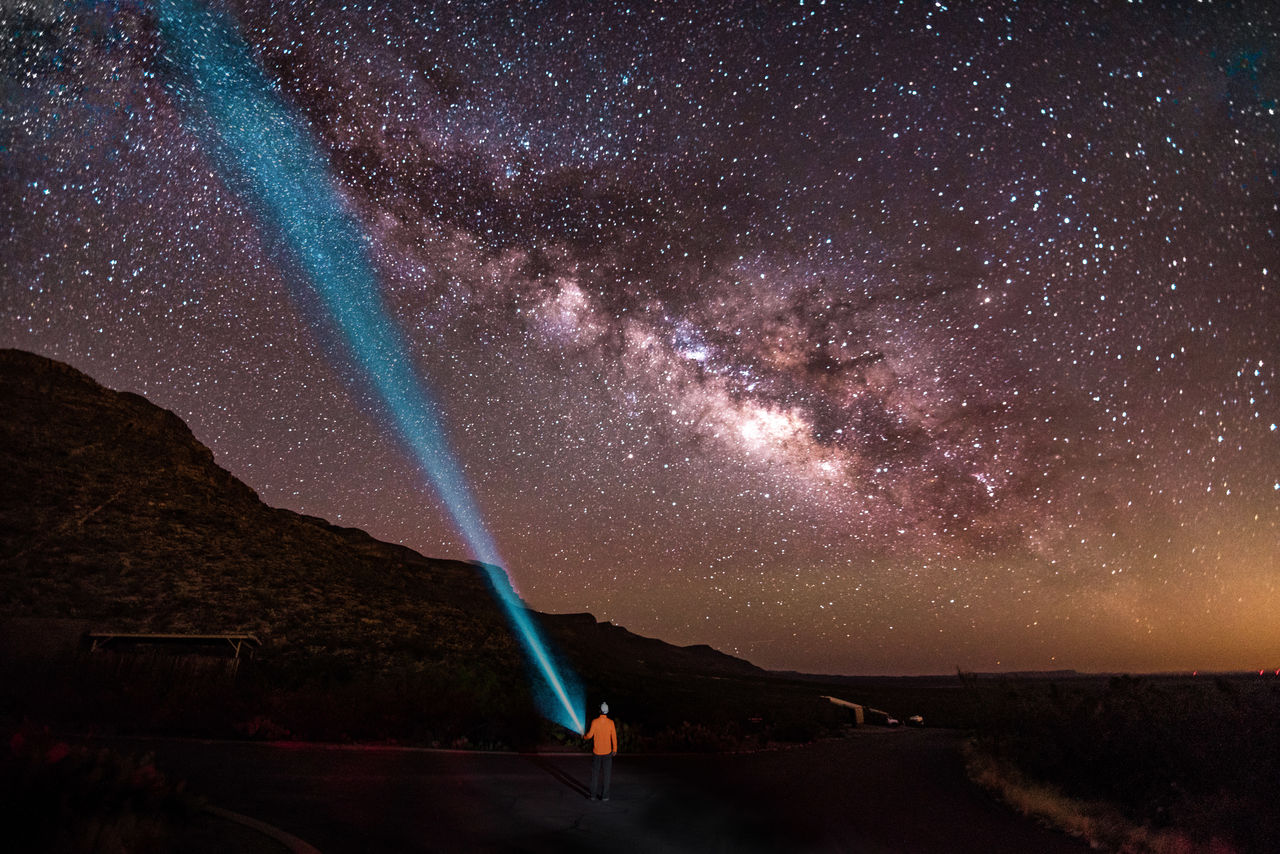 Rear View Of Man Holding Flashlight Against Star Field In Sky At Night