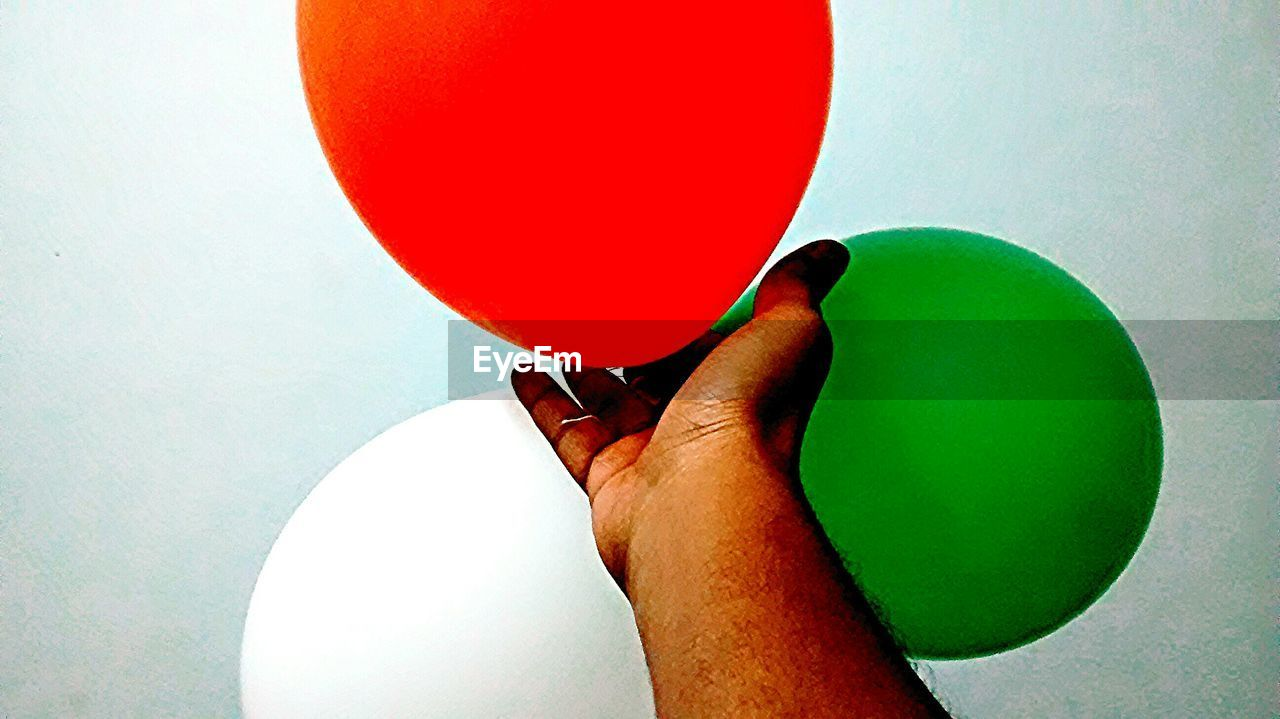 human hand, human body part, holding, ball, one person, red, balloon, indoors, playing, close-up, multi colored, real people, day, people