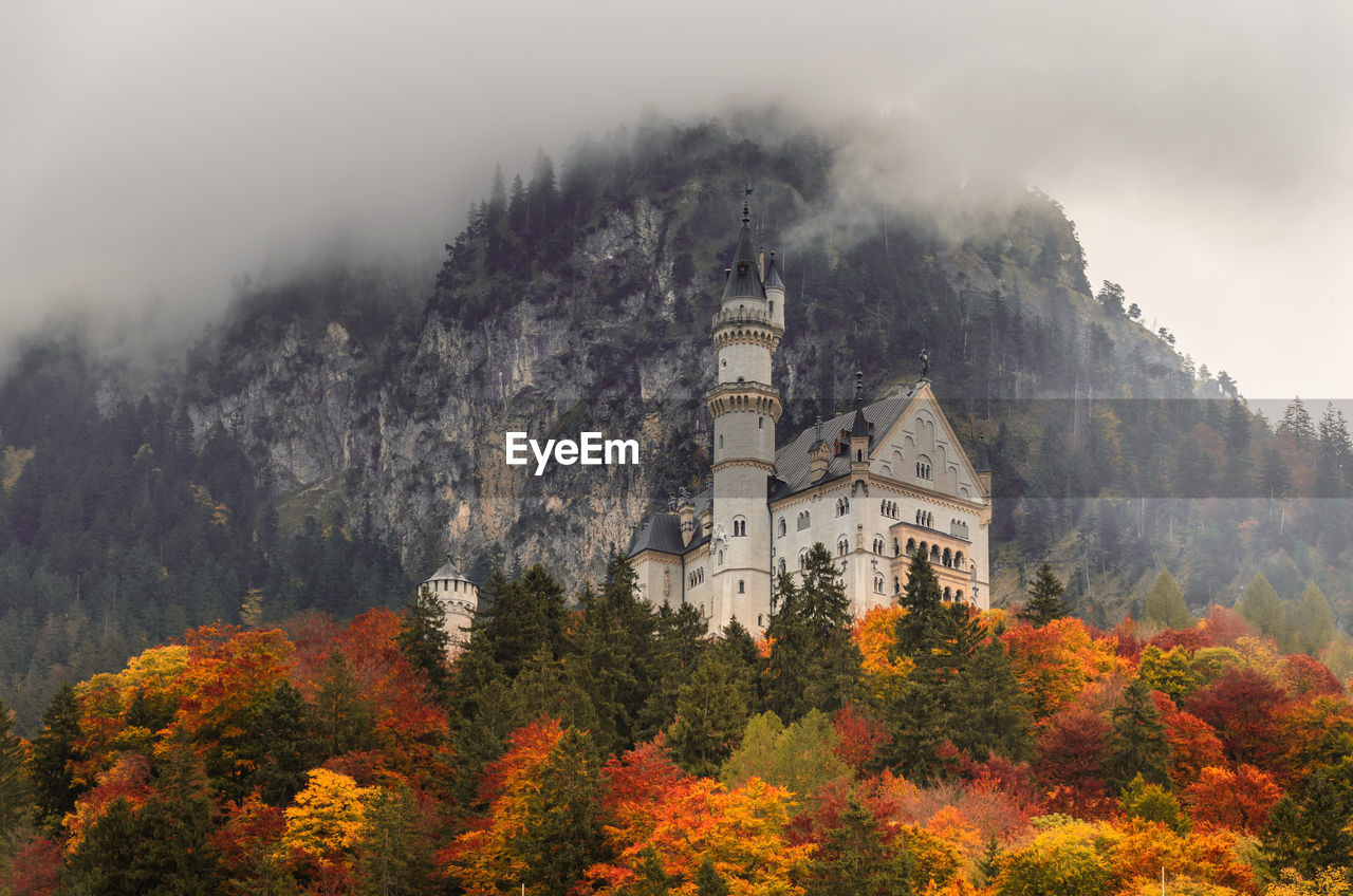 PANORAMIC VIEW OF TREES AND BUILDINGS AGAINST MOUNTAIN DURING AUTUMN