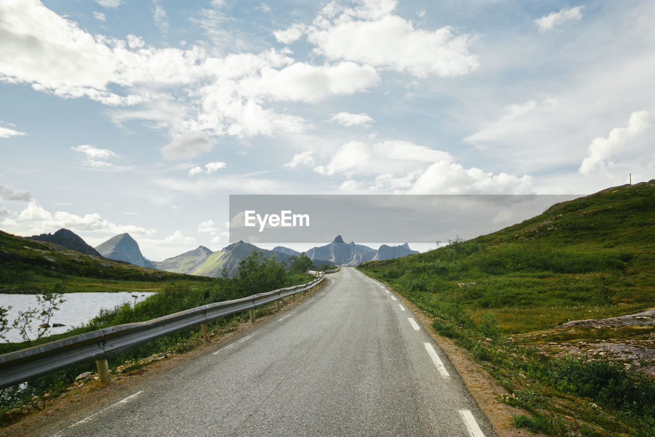 Empty Road Leading To Mountains Against Sky