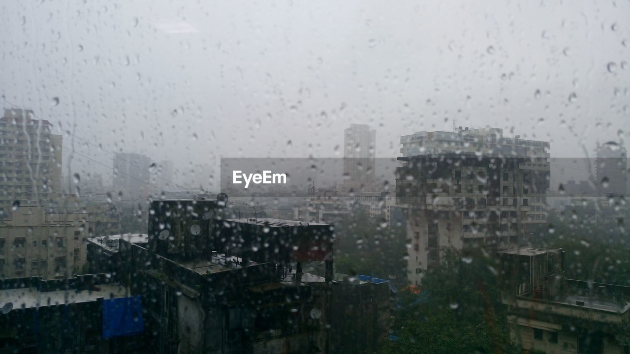 weather, rain, drop, wet, water, rainy season, raindrop, architecture, window, building exterior, rainfall, no people, built structure, focus on foreground, day, sky, fog, outdoors, city, cityscape, nature, bleak