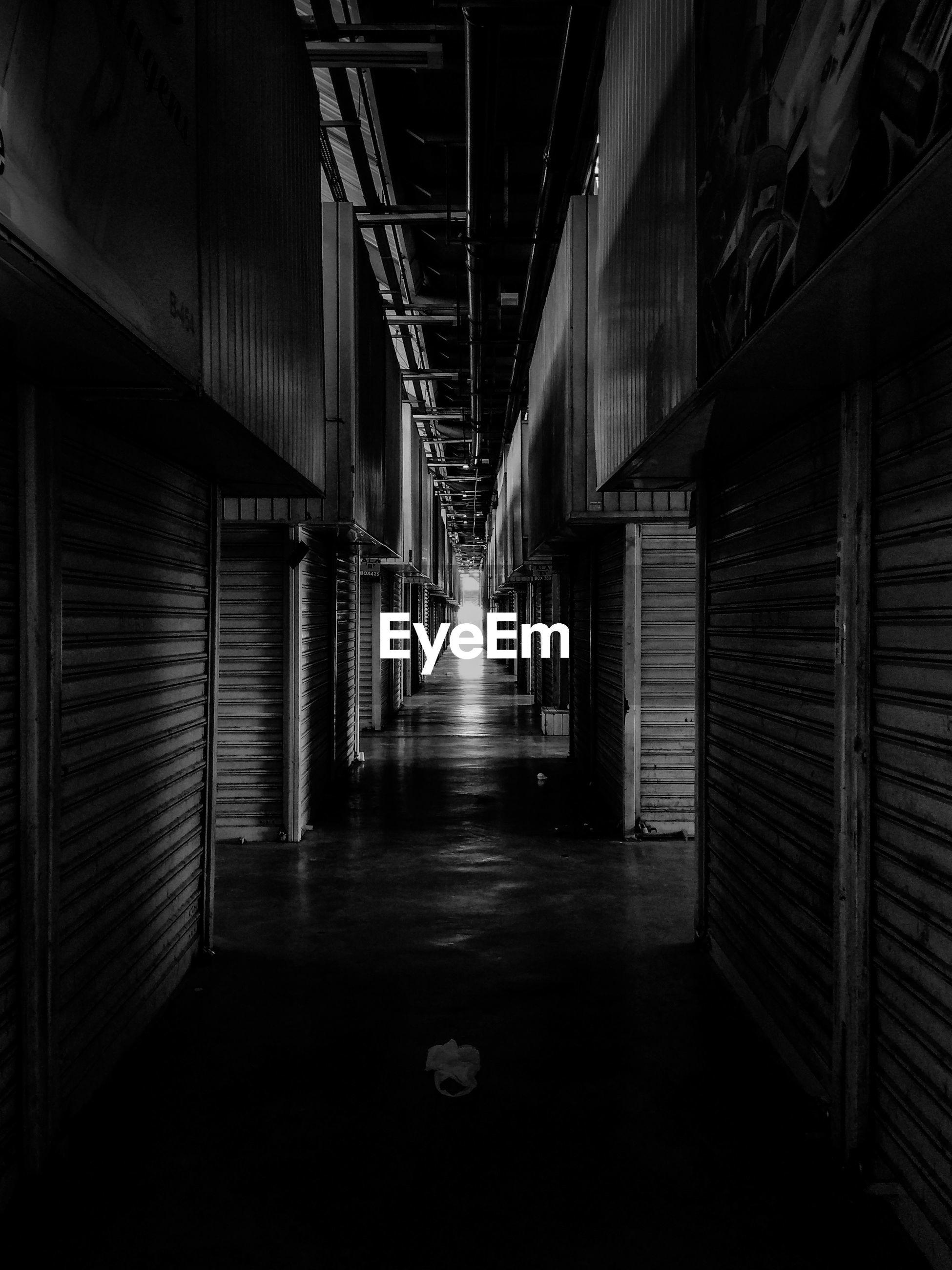 Empty corridor amidst stores in building