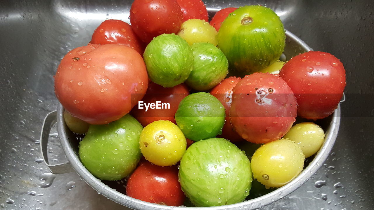 Close-Up Of Fresh Wet Tomatoes In Container On Sink