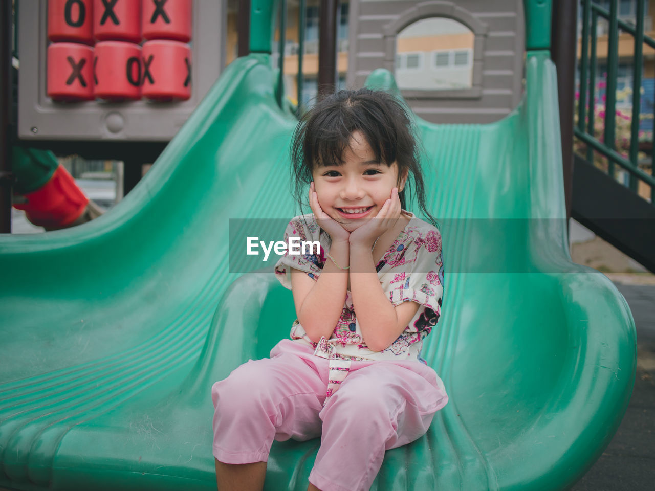 childhood, child, girls, one person, real people, happiness, front view, smiling, innocence, sitting, portrait, cute, looking at camera, leisure activity, lifestyles, enjoyment, emotion, women, bangs, outdoors, hairstyle, outdoor play equipment