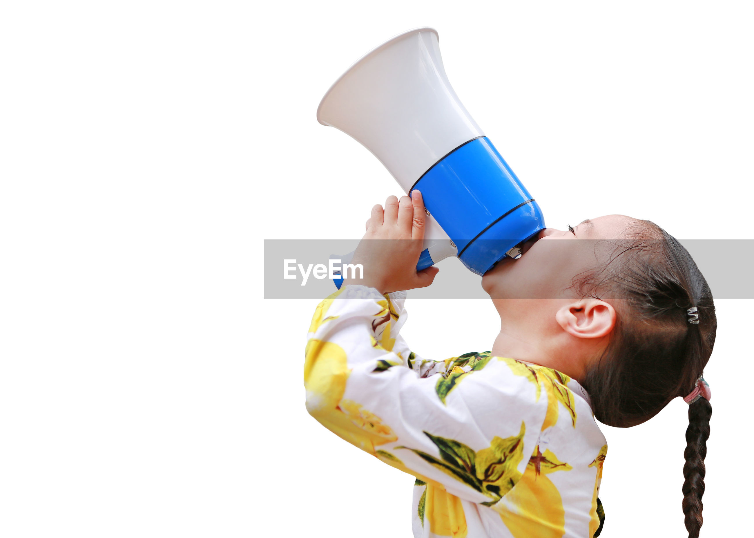 Side view of girl screaming in megaphone against white background