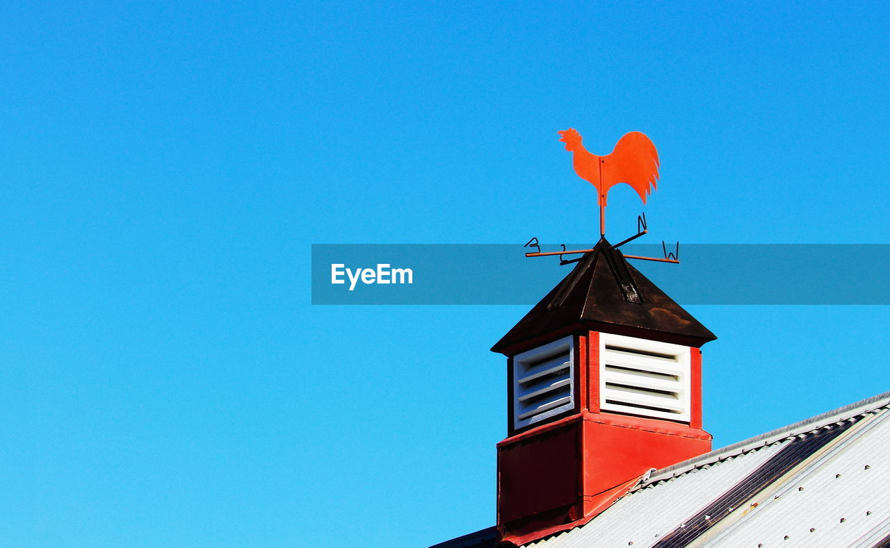 blue, red, architecture, copy space, sky, low angle view, clear sky, built structure, nature, building exterior, bird, day, no people, guidance, building, animal, animal themes, weather vane, vertebrate, outdoors
