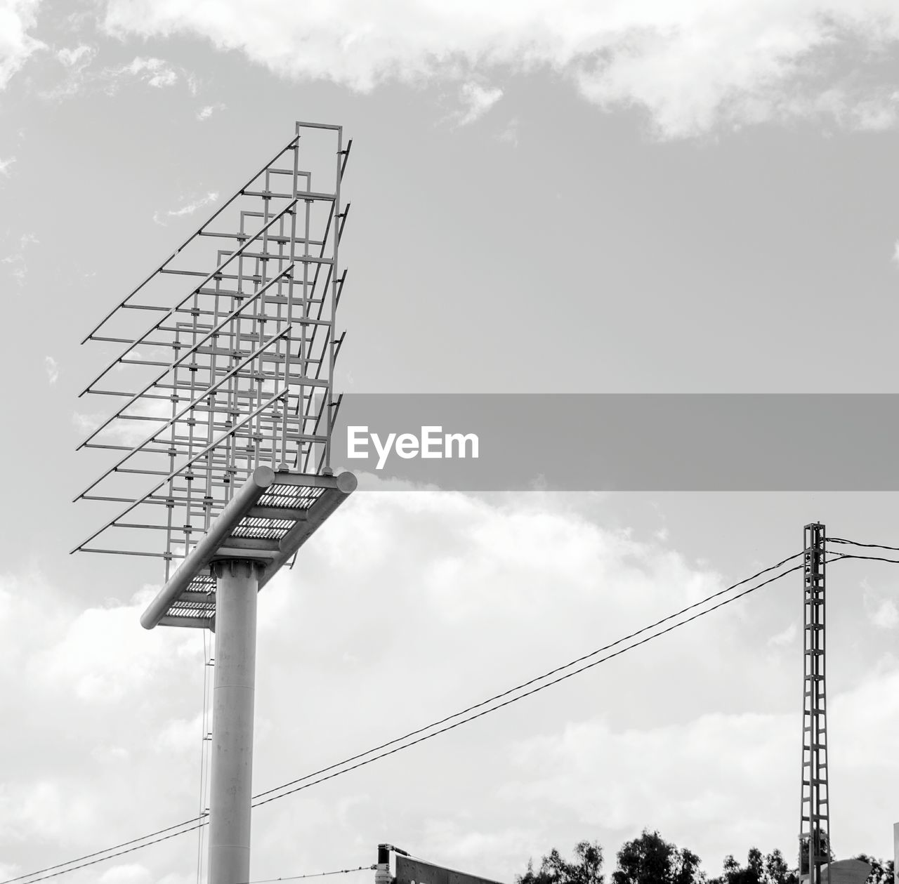 Low Angle View Of Steel Tower Against Cloudy Sky On Sunny Day