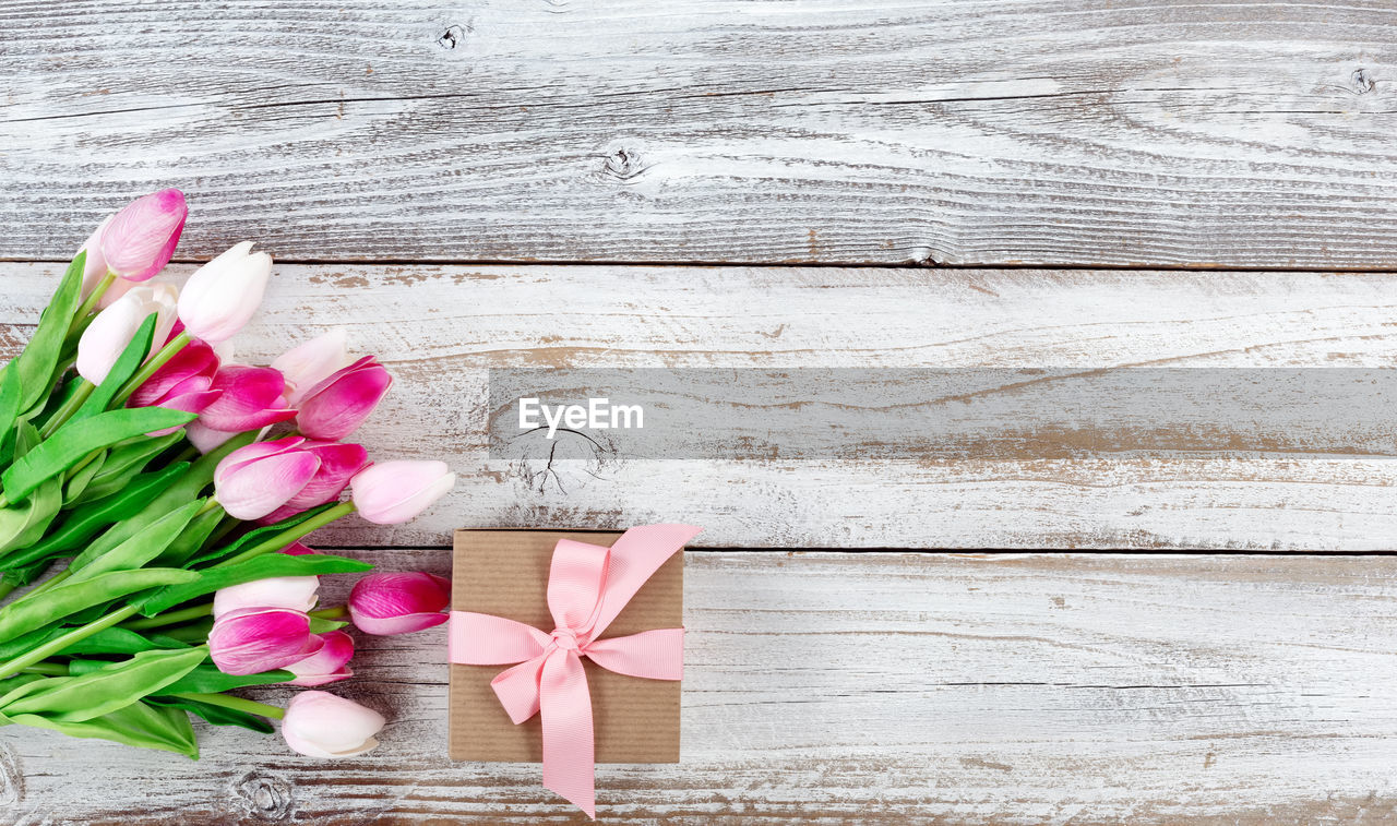 flower, flowering plant, wood - material, plant, table, freshness, petal, beauty in nature, pink color, vulnerability, no people, ribbon, fragility, still life, high angle view, nature, directly above, indoors, inflorescence, ribbon - sewing item, flower head