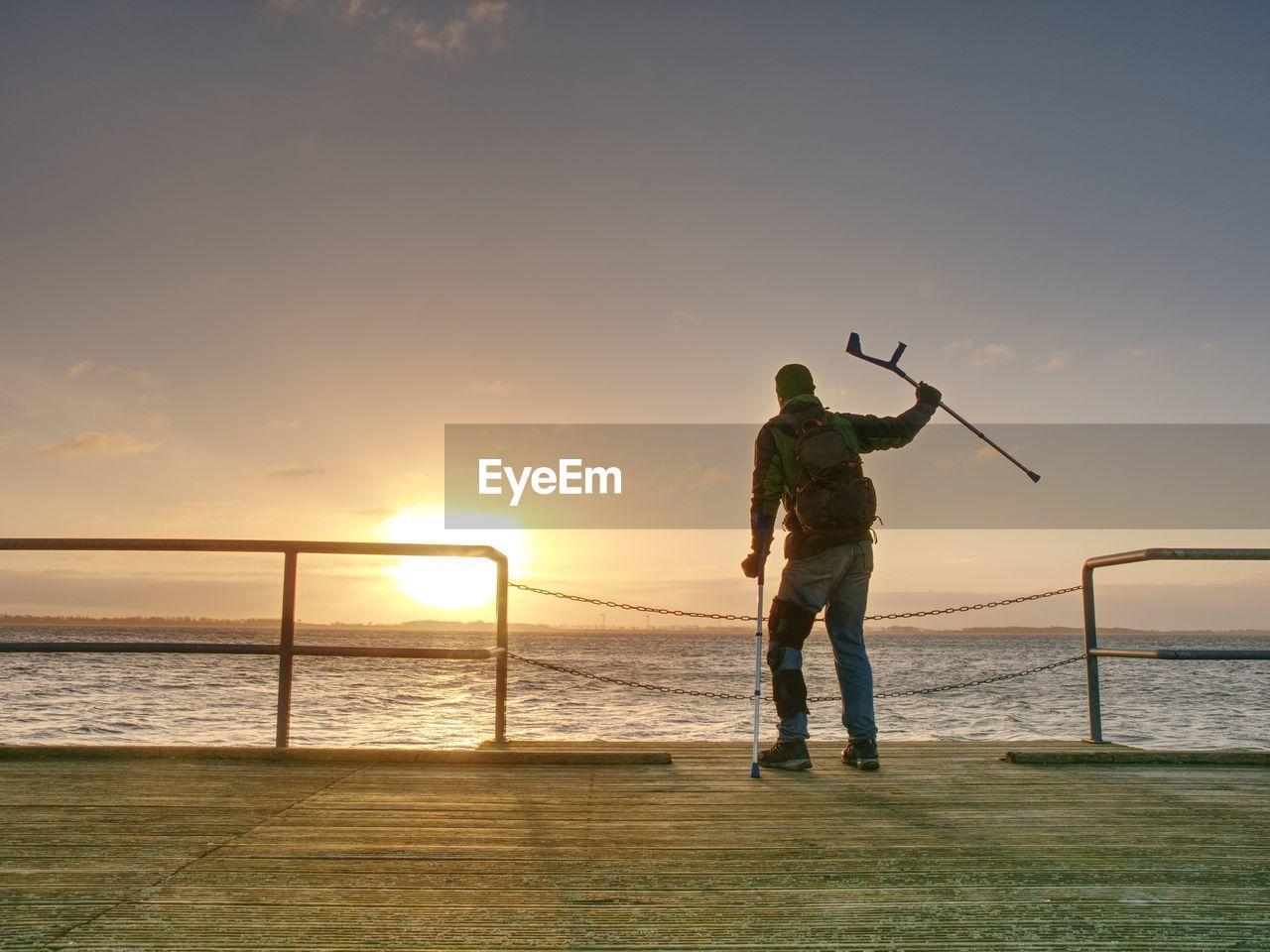 FULL LENGTH OF MAN STANDING AT BEACH AGAINST SKY DURING SUNSET