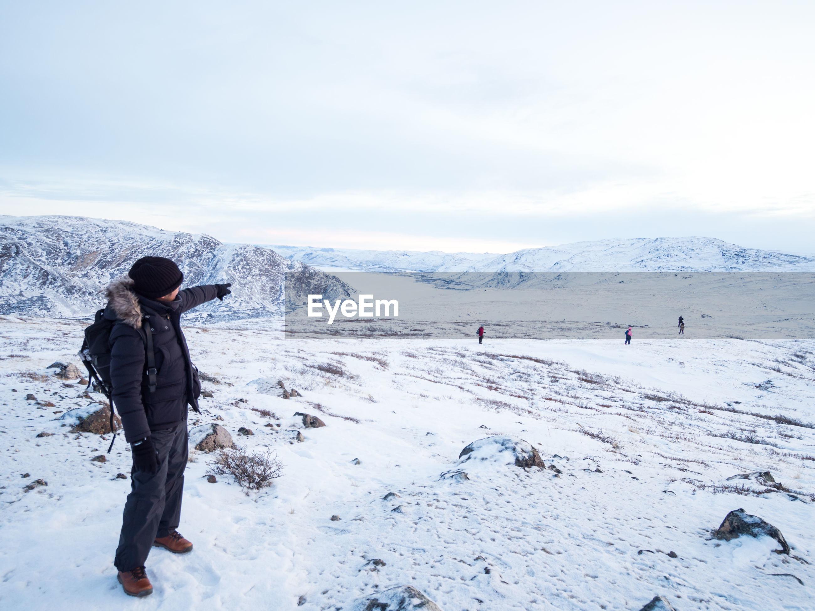 Full length of man on snow covered landscape against sky