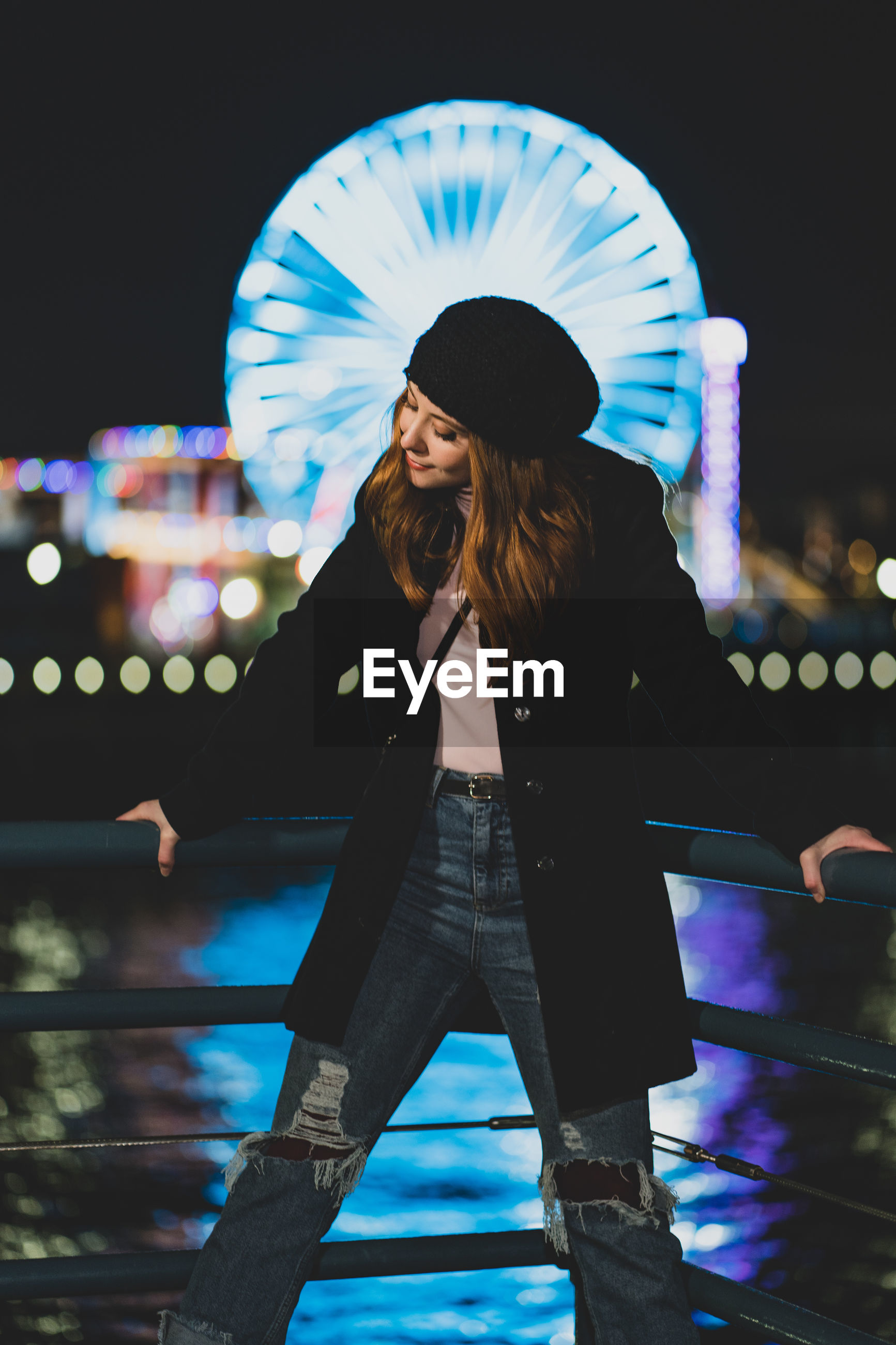real people, one person, leisure activity, lifestyles, night, standing, three quarter length, illuminated, casual clothing, focus on foreground, architecture, women, young adult, built structure, adult, railing, hair, long hair, young women, hairstyle, outdoors