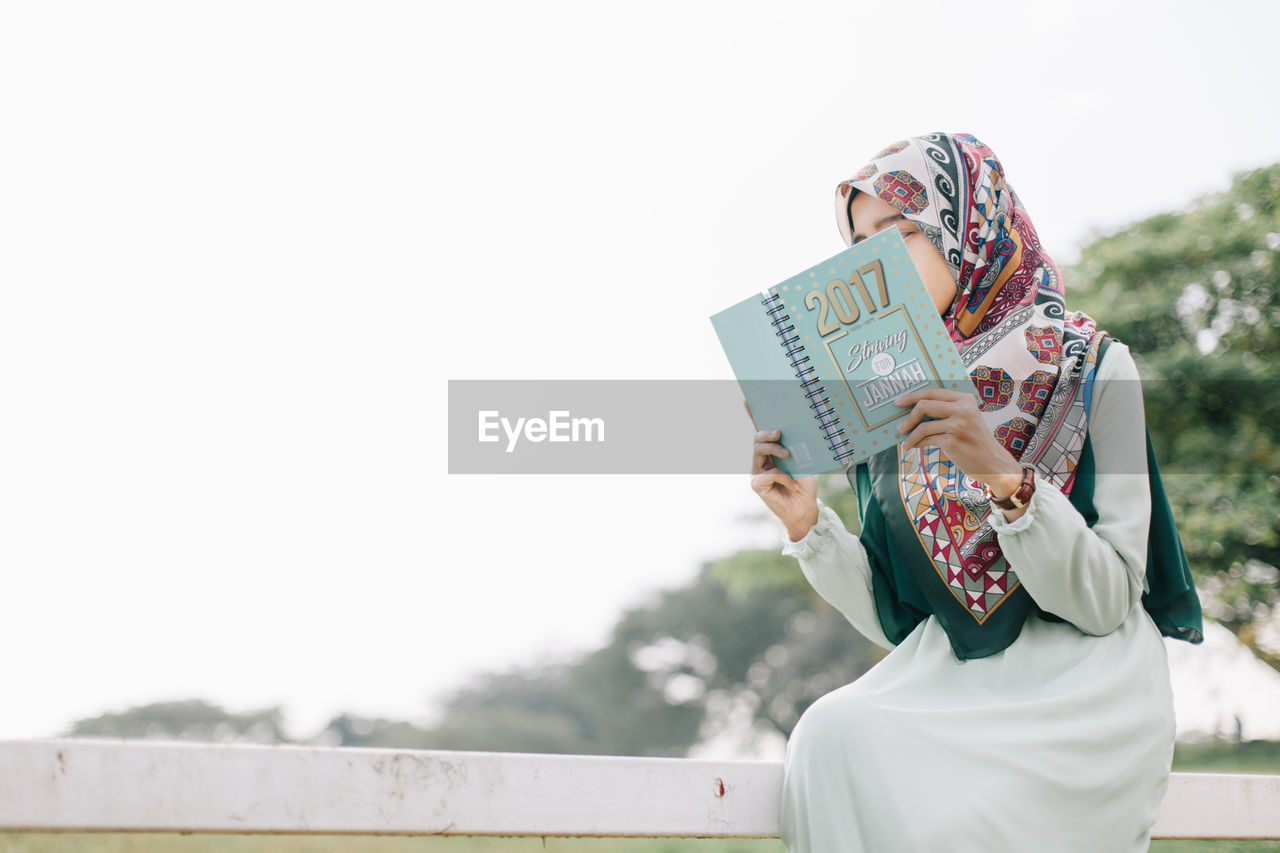 LOW ANGLE VIEW OF WOMAN HOLDING BOOK