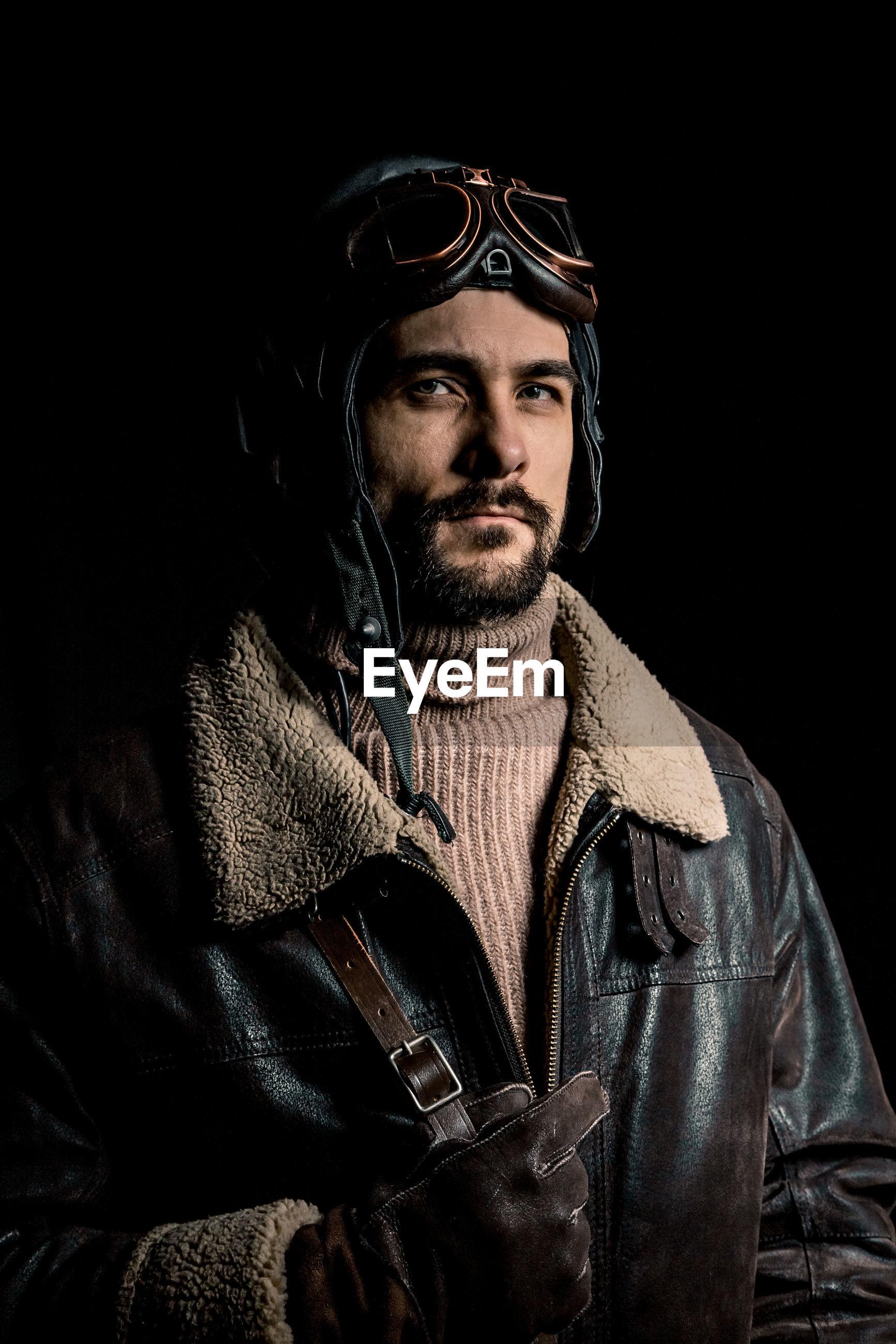 Portrait of handsome mid adult man wearing leather jacket standing against black background