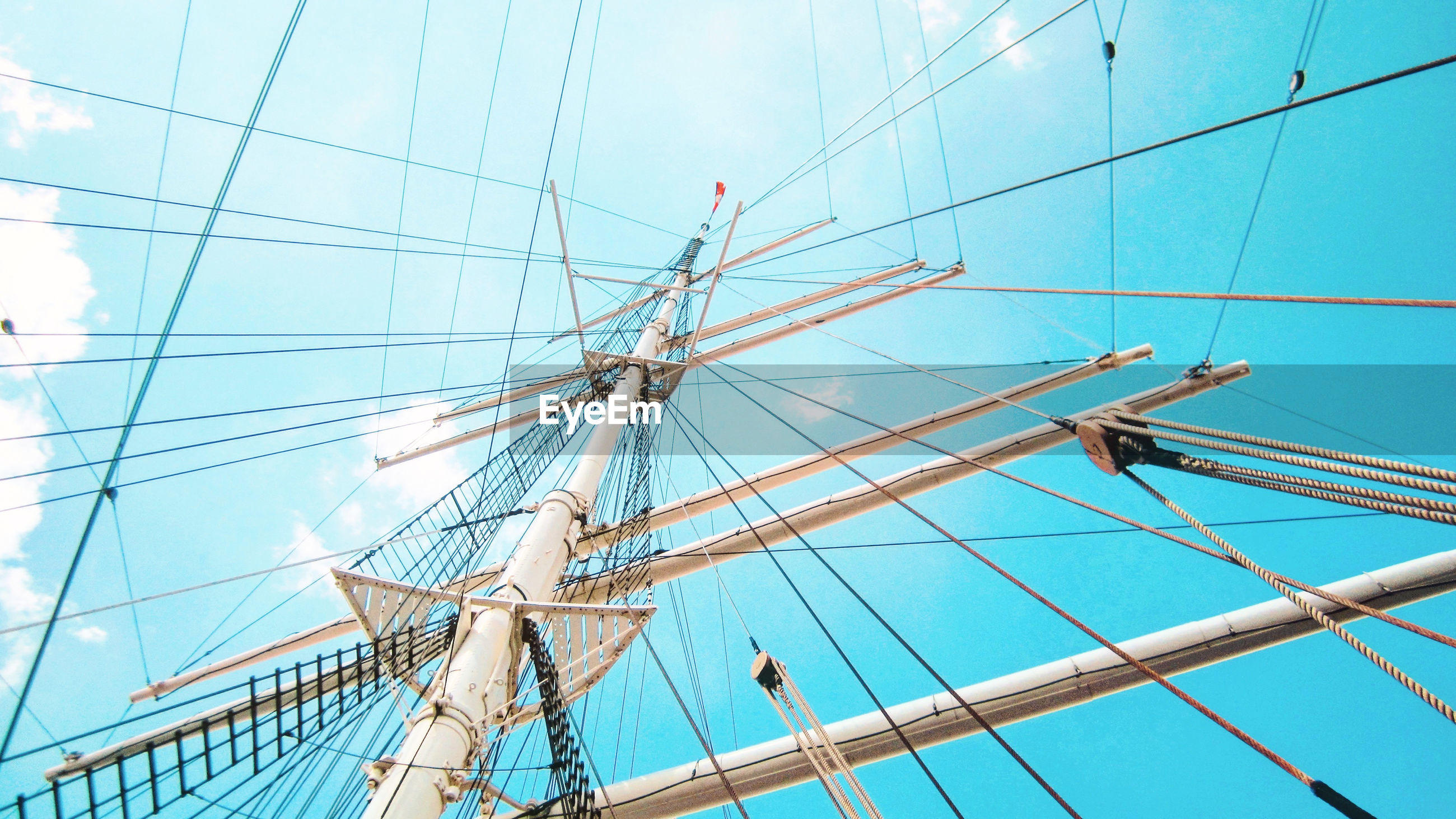 LOW ANGLE VIEW OF SAILBOAT ON MAST AGAINST BLUE SKY