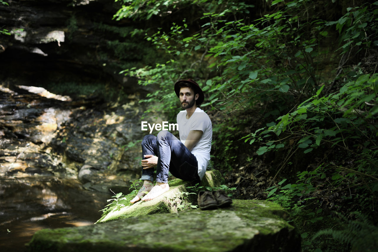 Young Man Sitting On Rock In Forest