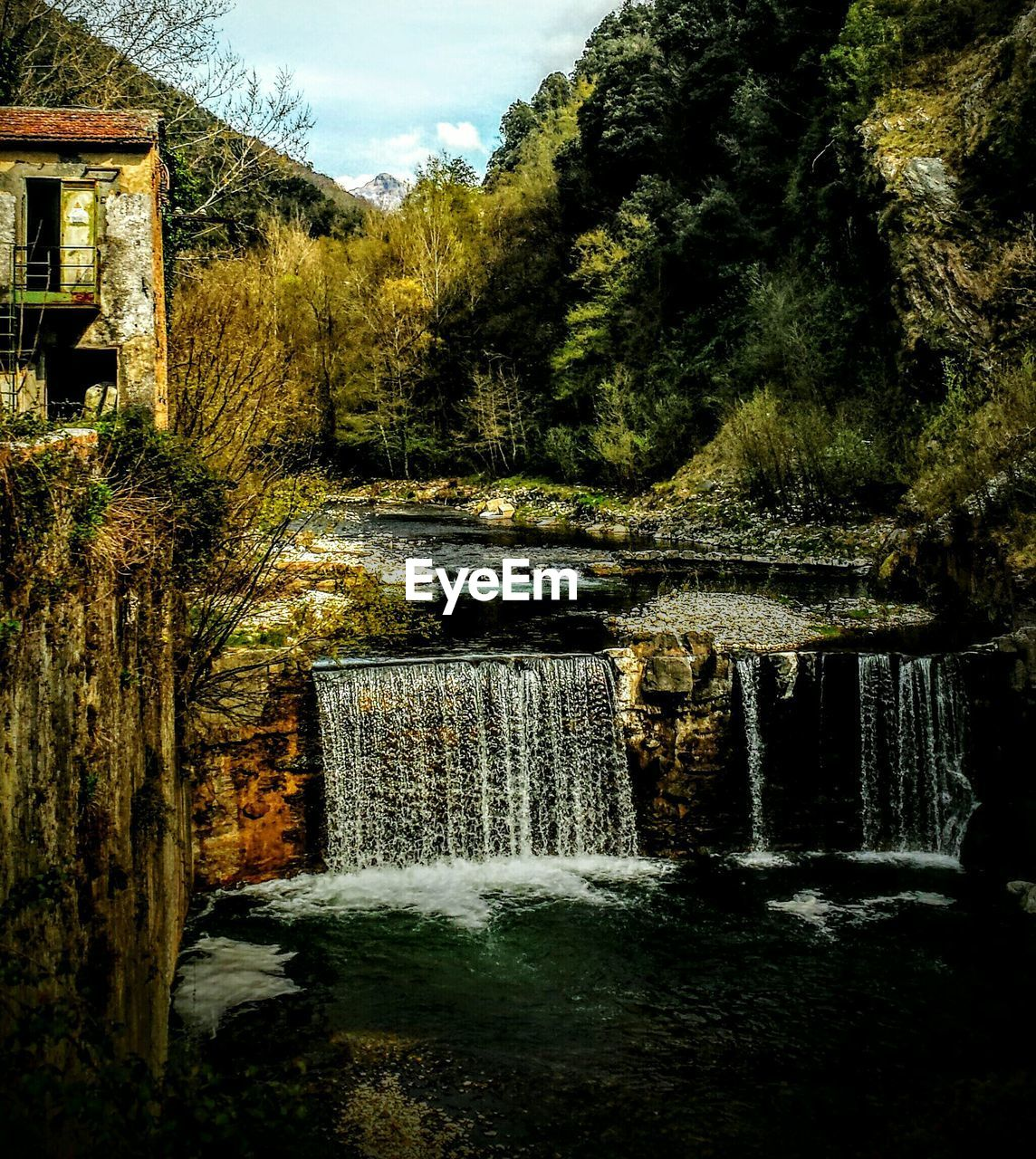 water, motion, waterfall, flowing water, tree, nature, long exposure, outdoors, beauty in nature, day, no people, scenics, forest, built structure, architecture, tranquility, waterfront, sky, watermill