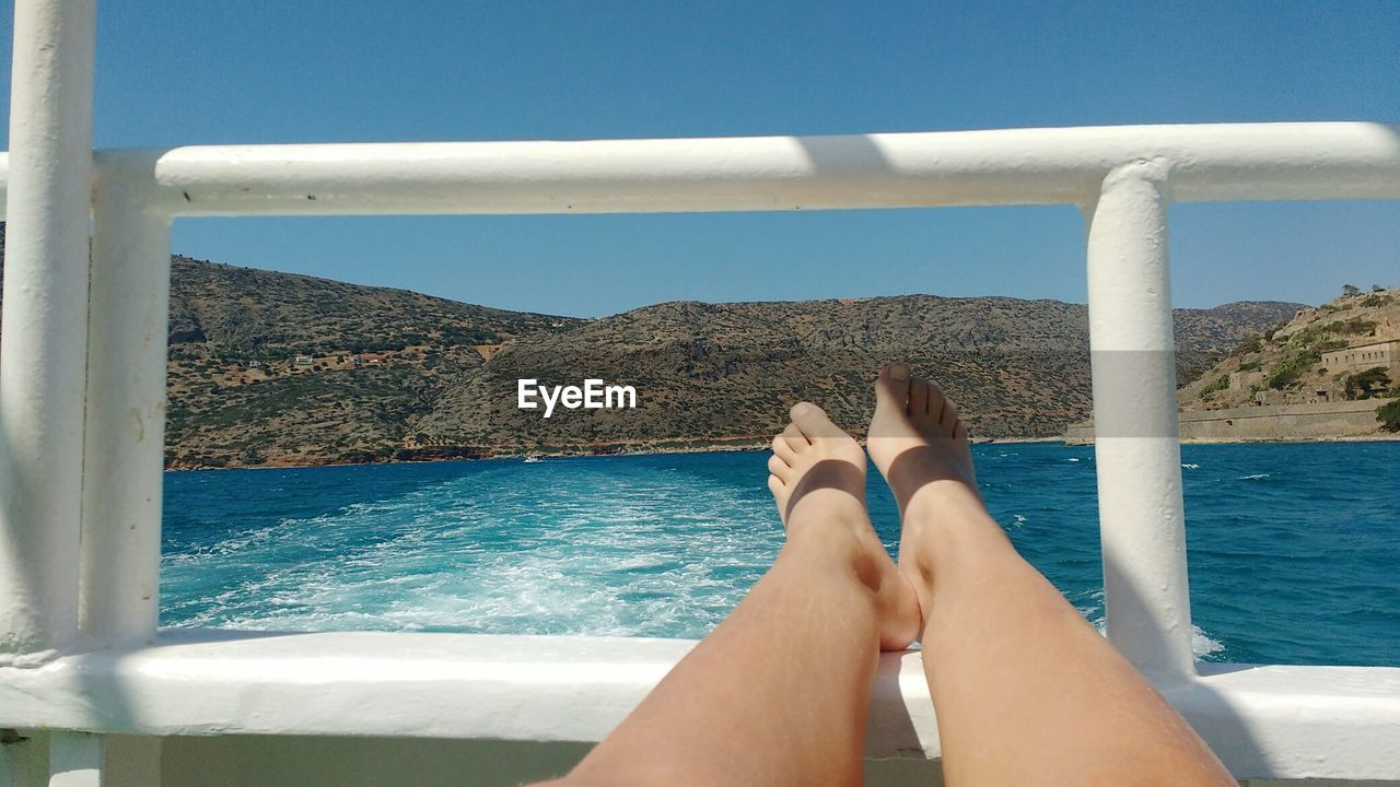 Low section of woman relaxing in boat on sea