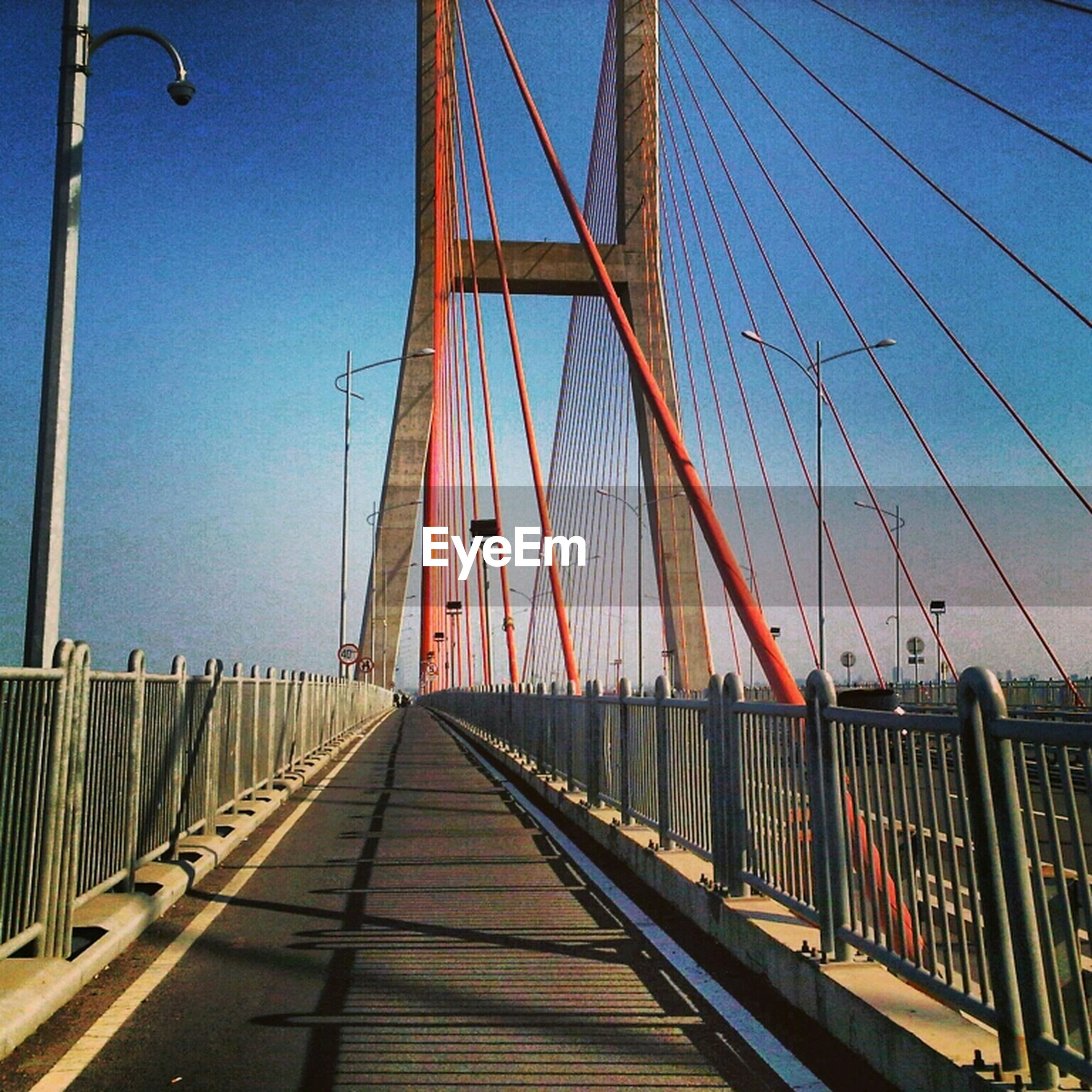 connection, built structure, architecture, transportation, bridge - man made structure, the way forward, suspension bridge, engineering, clear sky, diminishing perspective, bridge, sky, low angle view, blue, cable, long, railing, vanishing point, outdoors, day