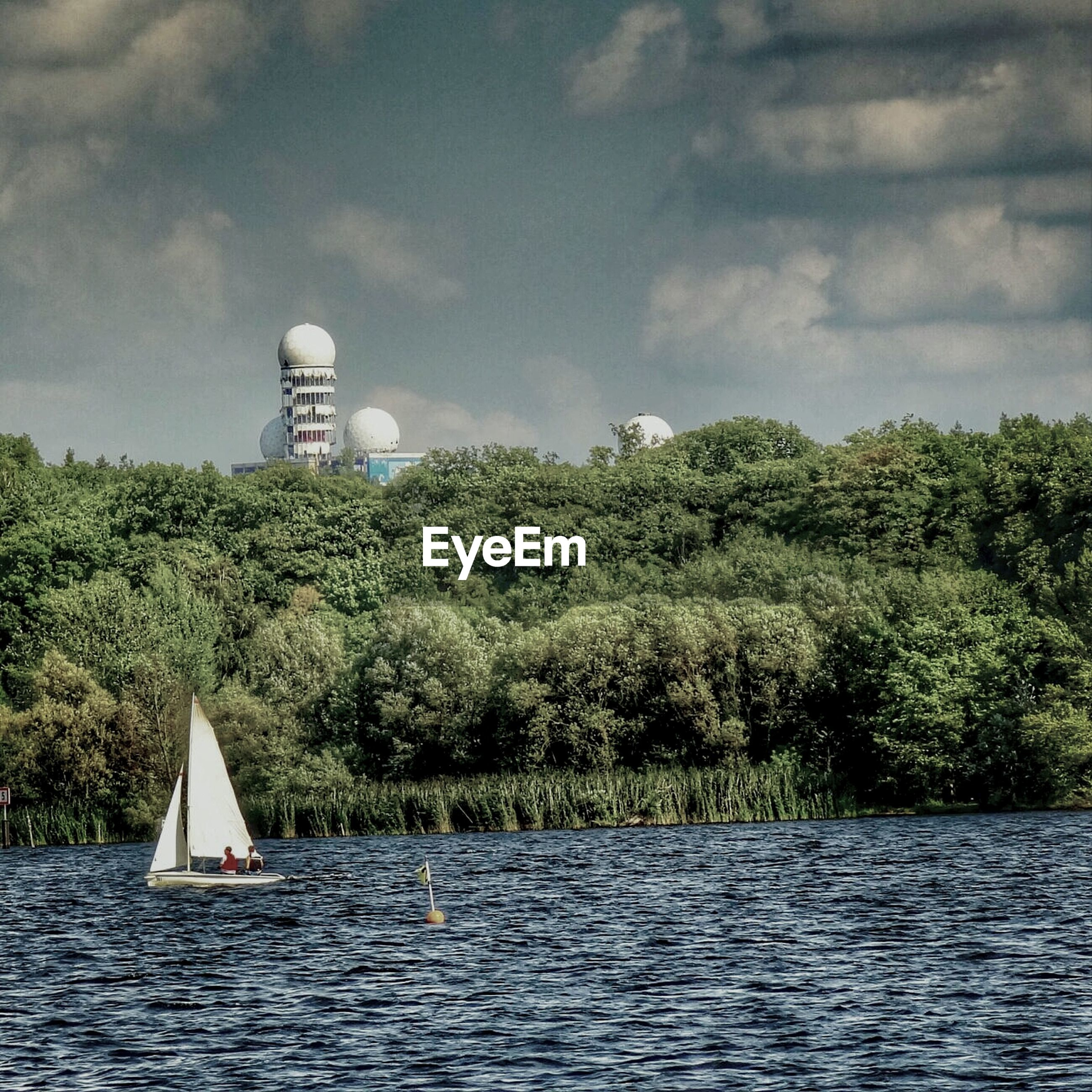 Sailboat sailing on lake and nsa listening station on teufelsberg against cloudy sky