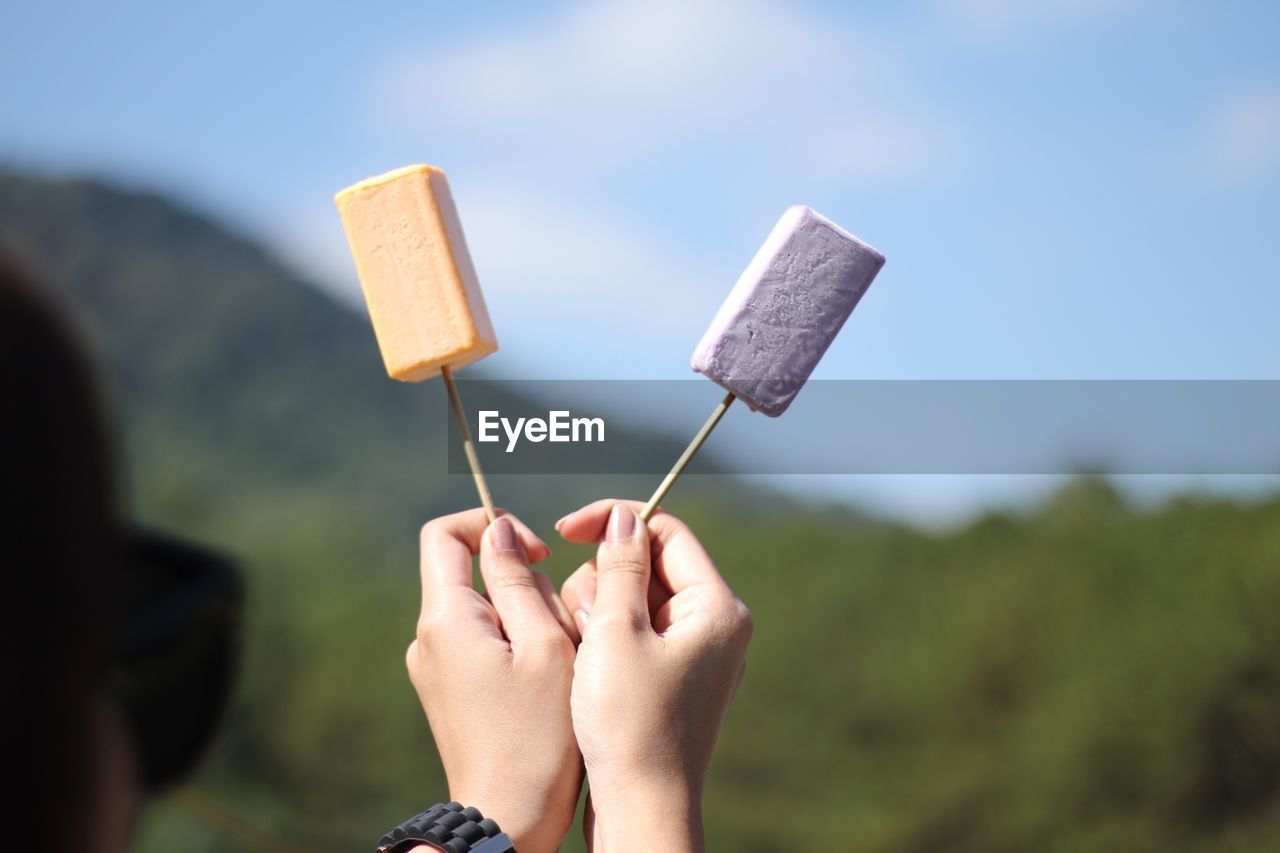 Close-up of hand holding popsicles against sky