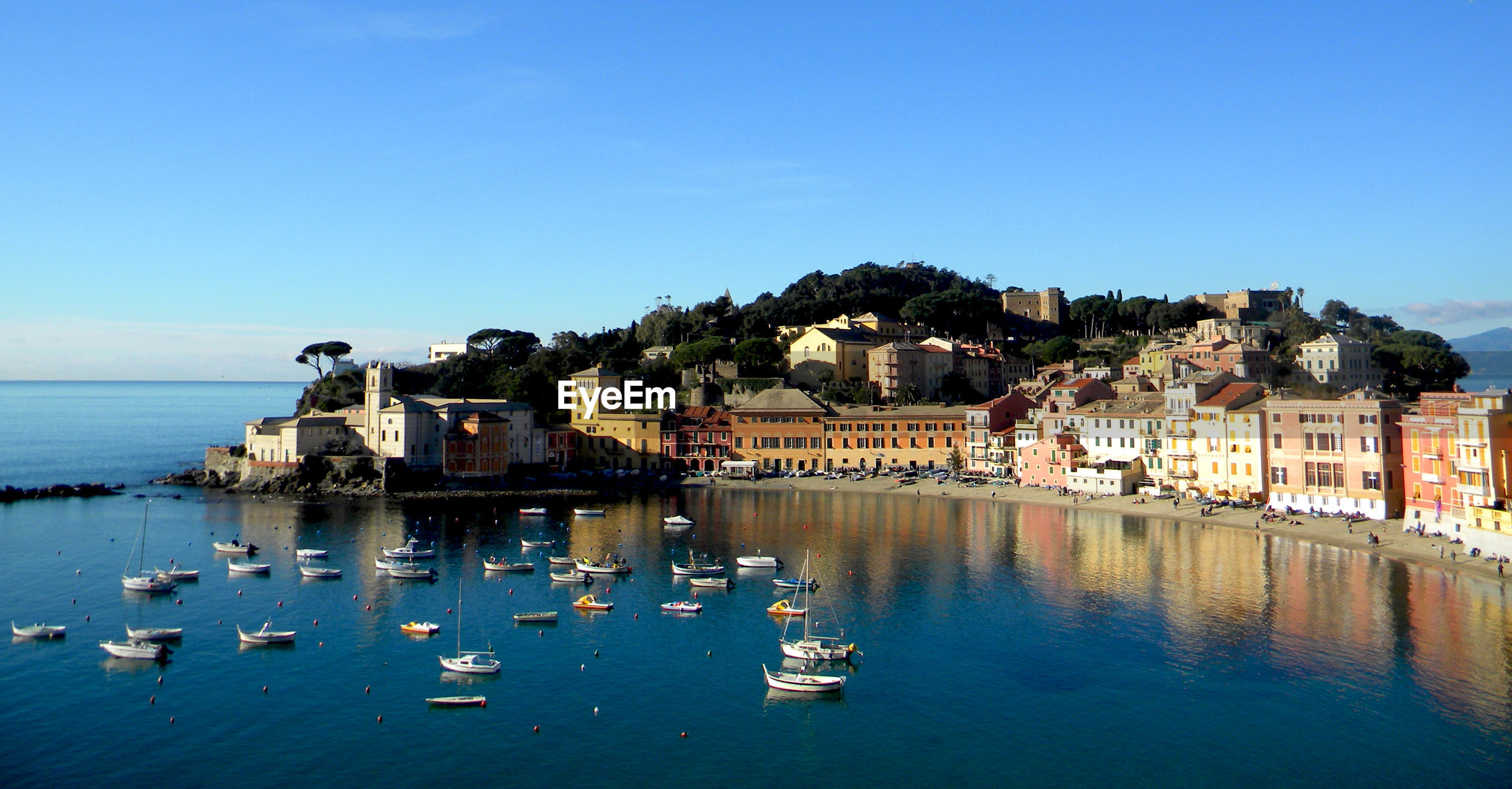 Scenic view of sea and buildings against clear blue sky