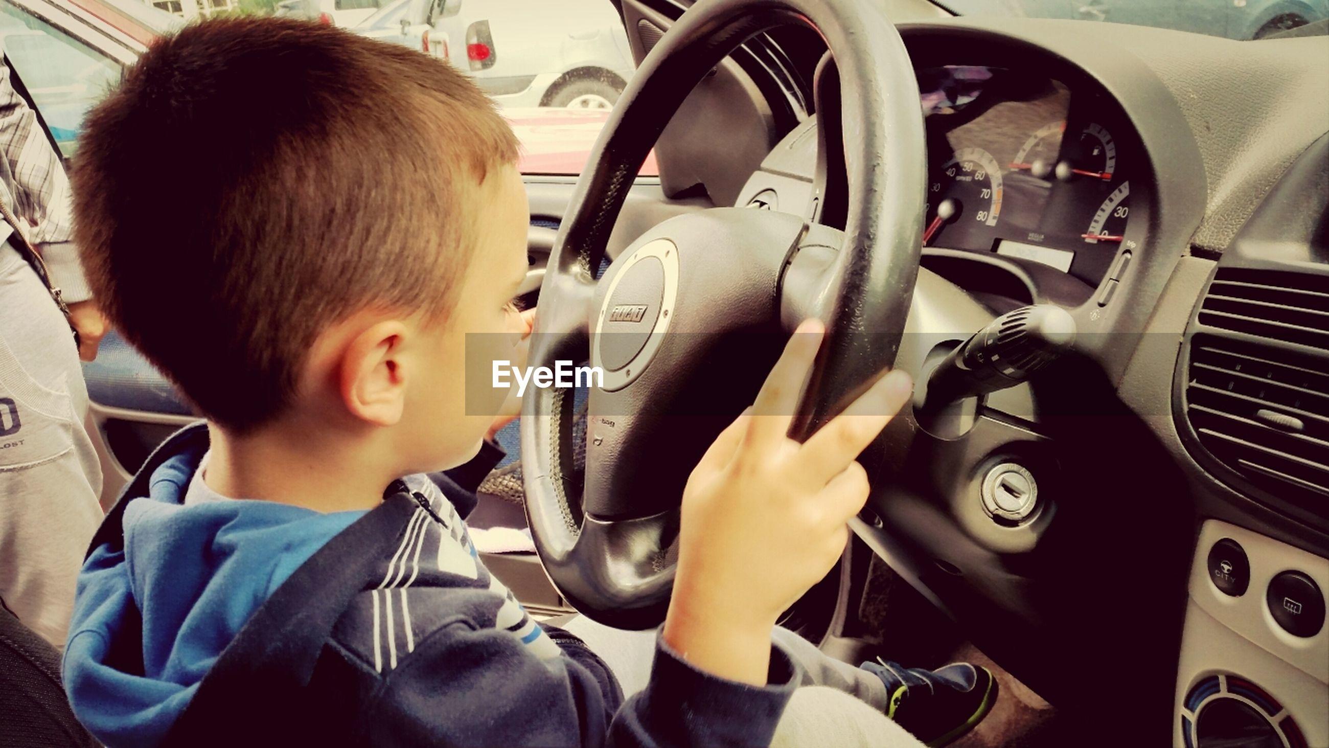 Boy at car's steering wheel