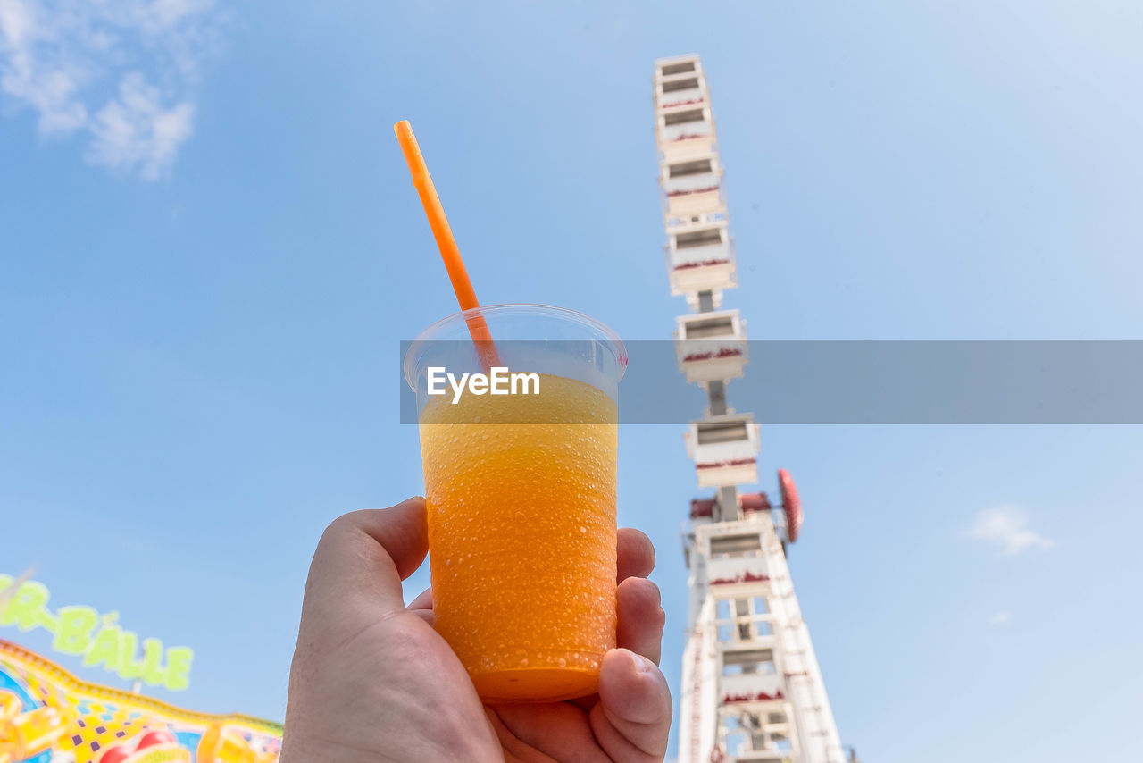 Cropped hand holding juice glass against ferris wheel in city