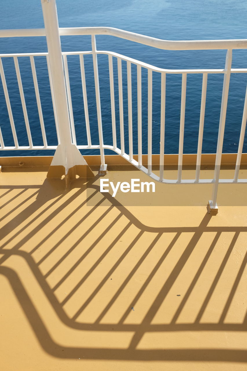 sea, railing, sunlight, shadow, water, no people, high angle view, day, outdoors, beach, nature, beauty in nature