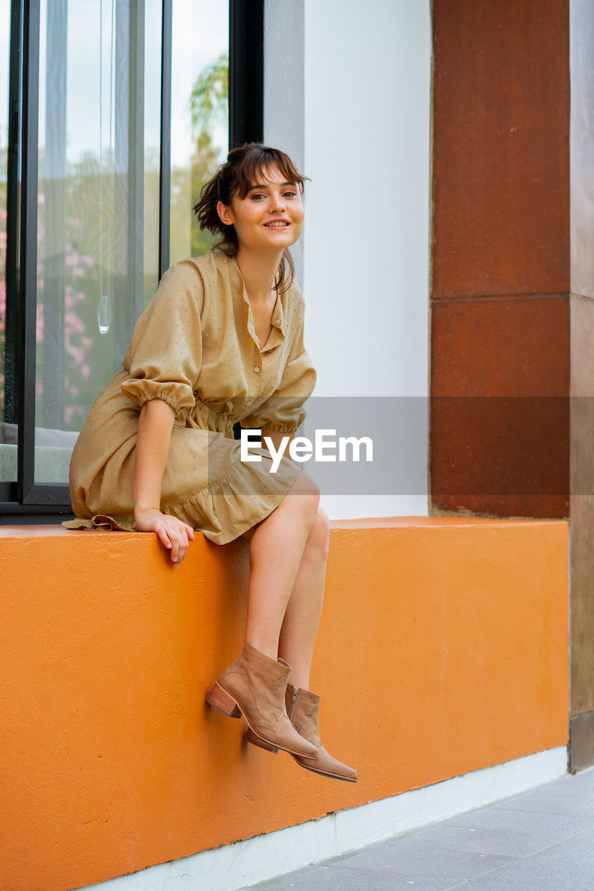 Portrait of smiling woman sitting against wall, wearing a beige dress and cowboy-style heels.