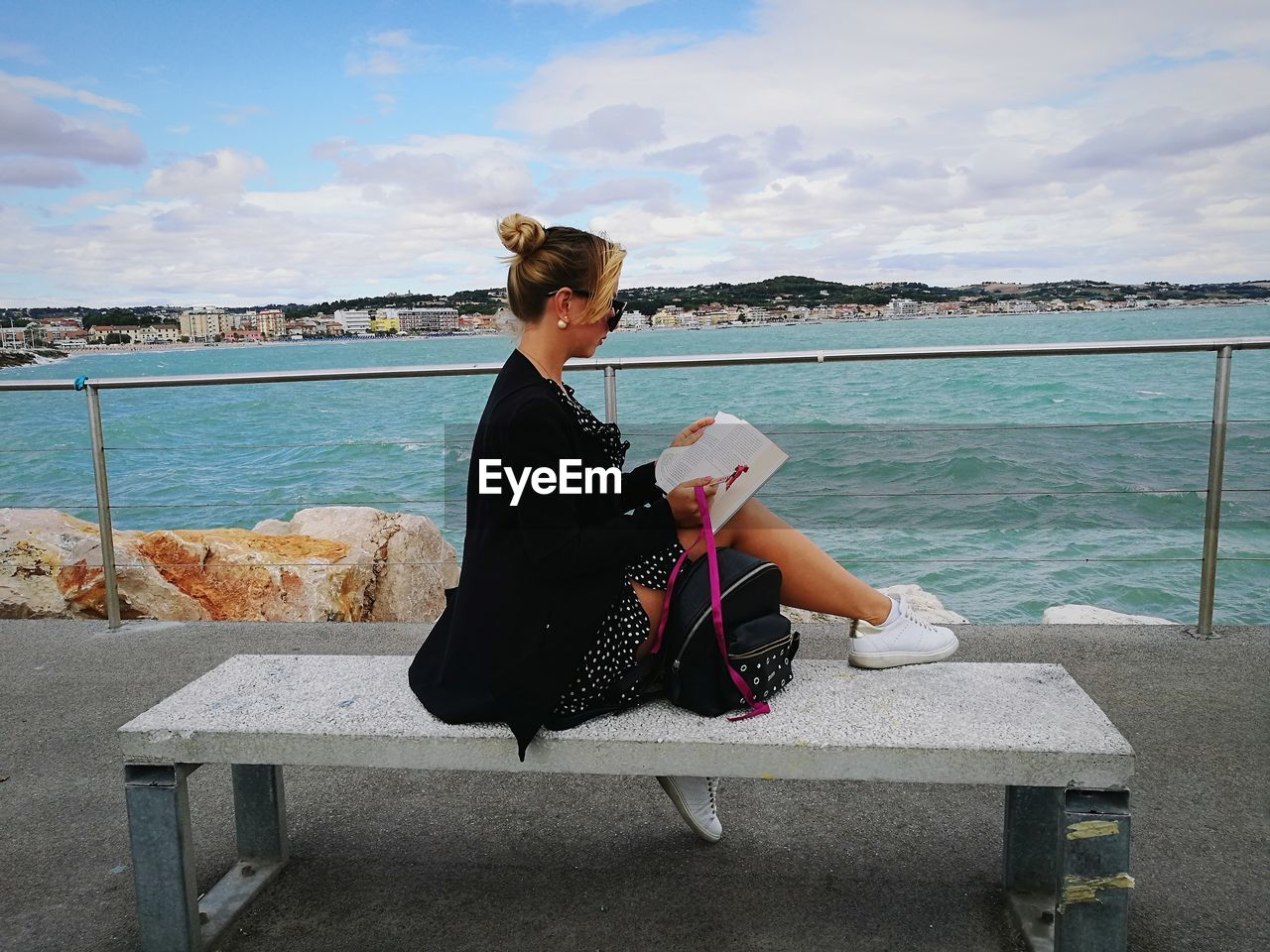 Woman sitting on seat at promenade against sky